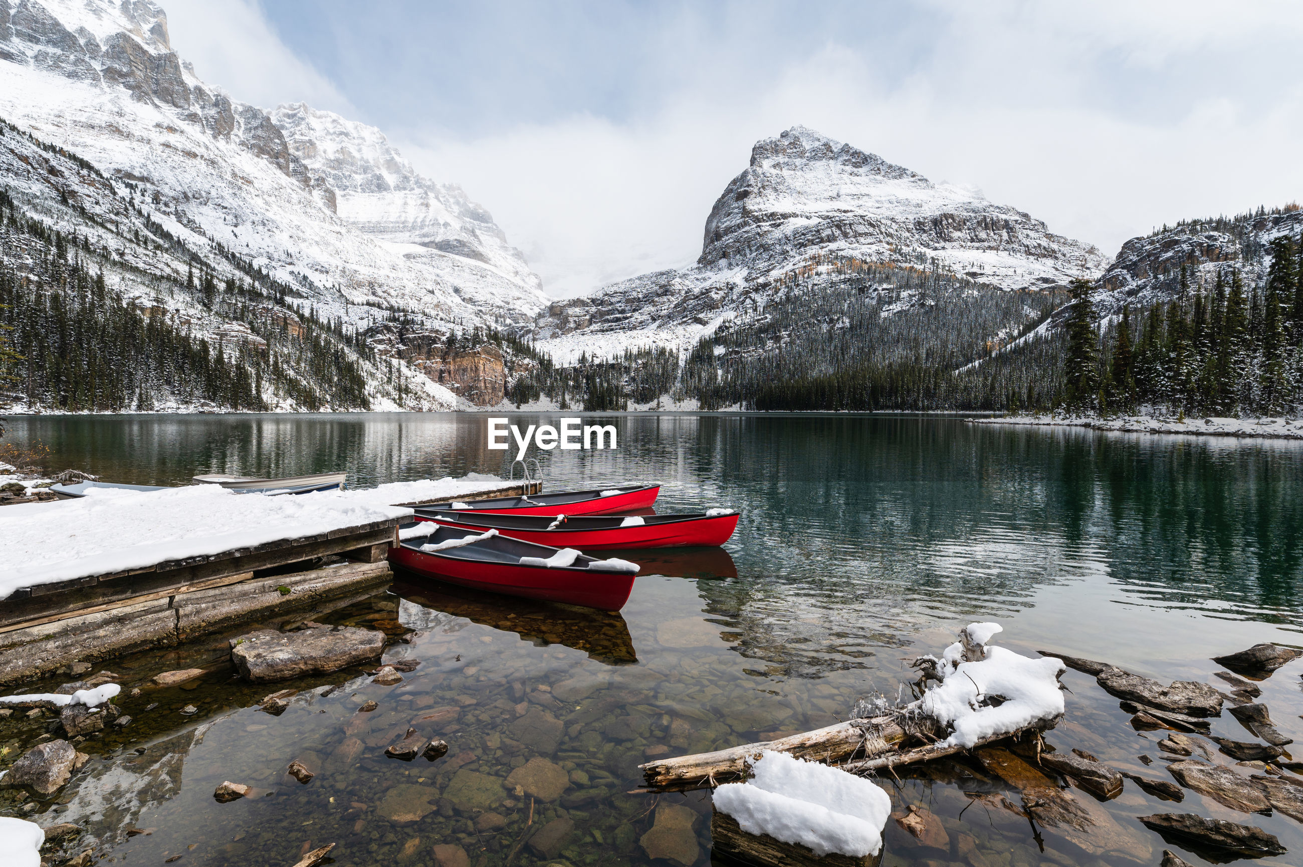 BOAT FLOATING ON LAKE AGAINST SNOWCAPPED MOUNTAINS