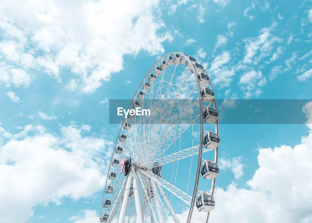 amusement park ride, amusement park, ferris wheel, cloud - sky, sky, arts culture and entertainment, fairground, low angle view, large, day, nature, leisure activity, shape, circle, outdoors, no people, geometric shape, built structure, enjoyment, traveling carnival