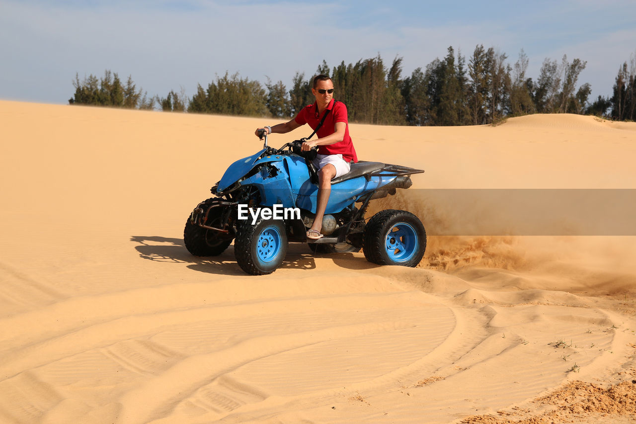 Man Riding Motorcycle On Sand