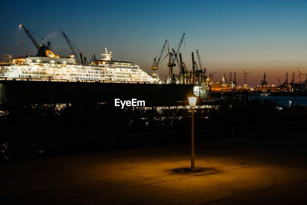 Ship moored on illuminated harbor against sky at dusk