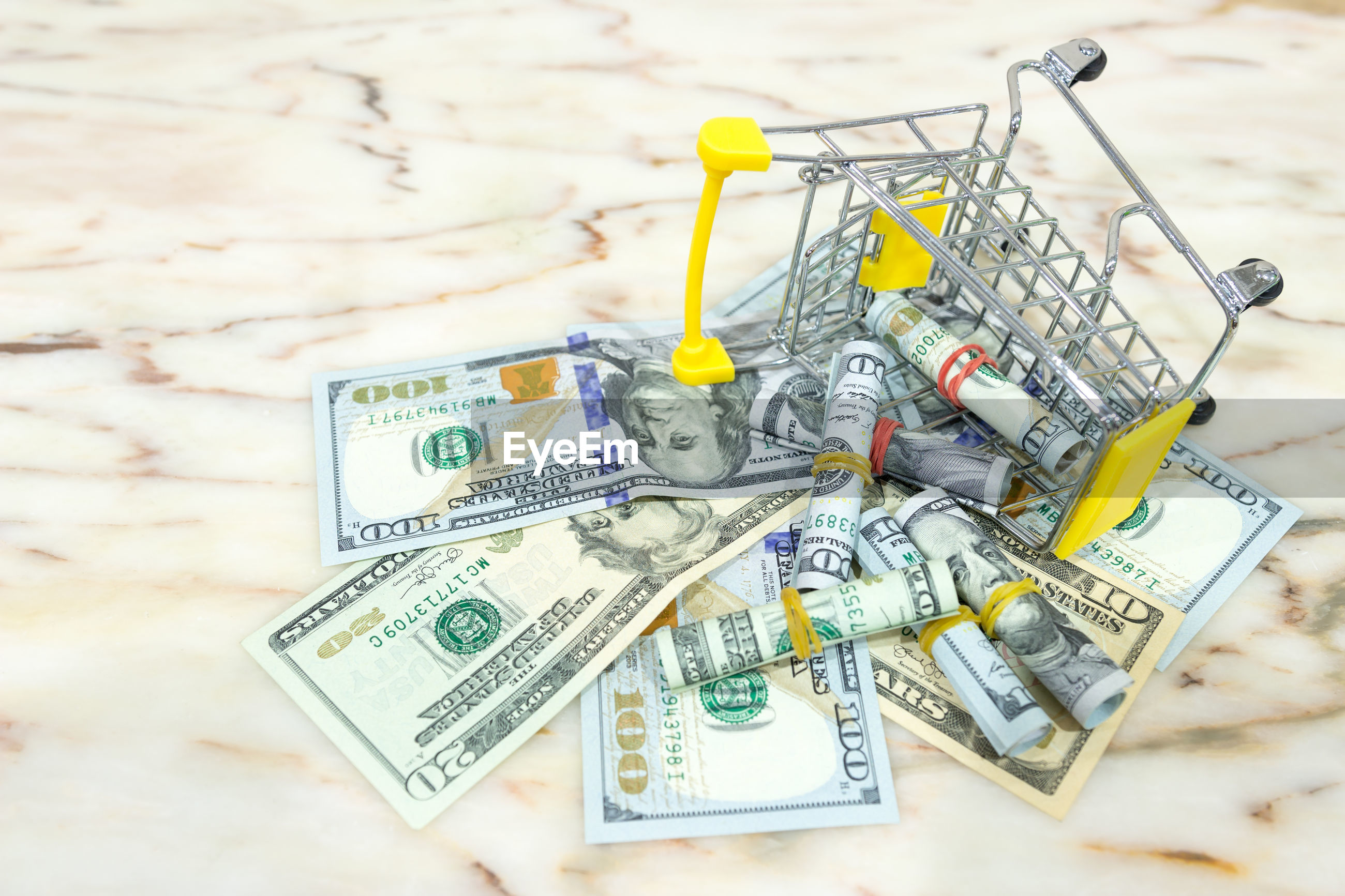 High angle view of small shopping cart with paper currencies on table