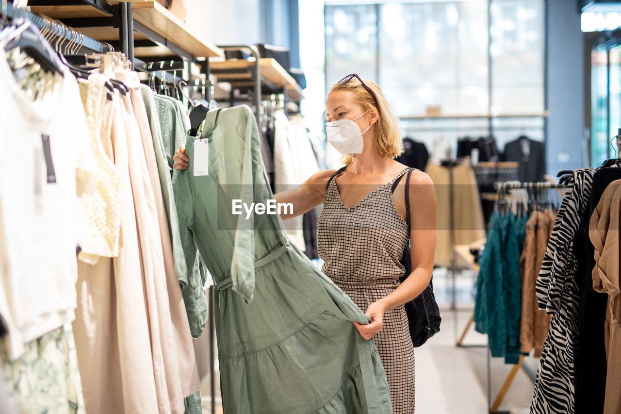 Woman wearing mask shopping at store
