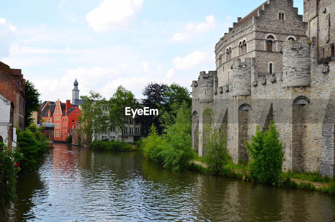 Castle By Canal Against Sky