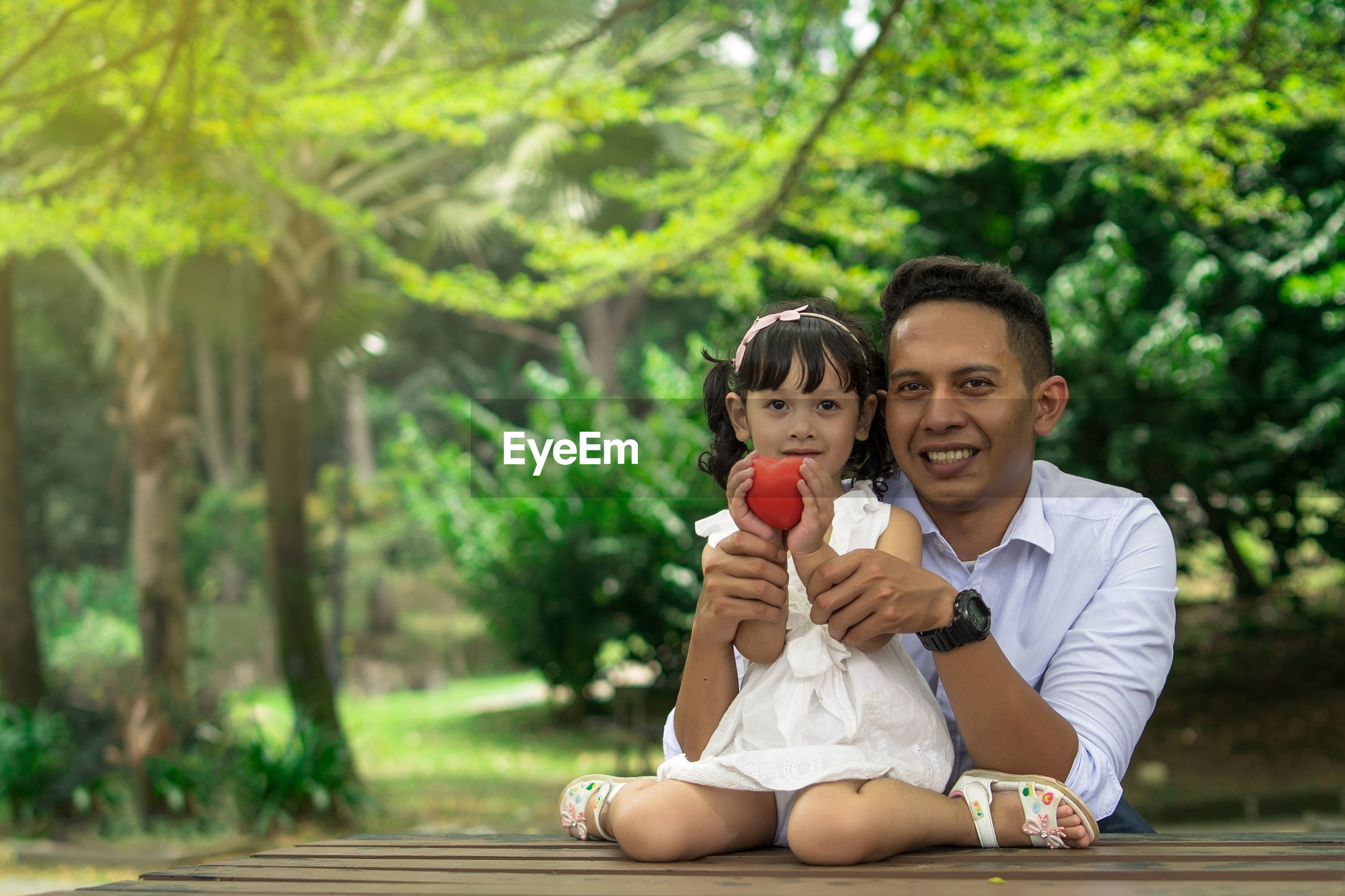 Portrait of father and daughter with heart shape against trees