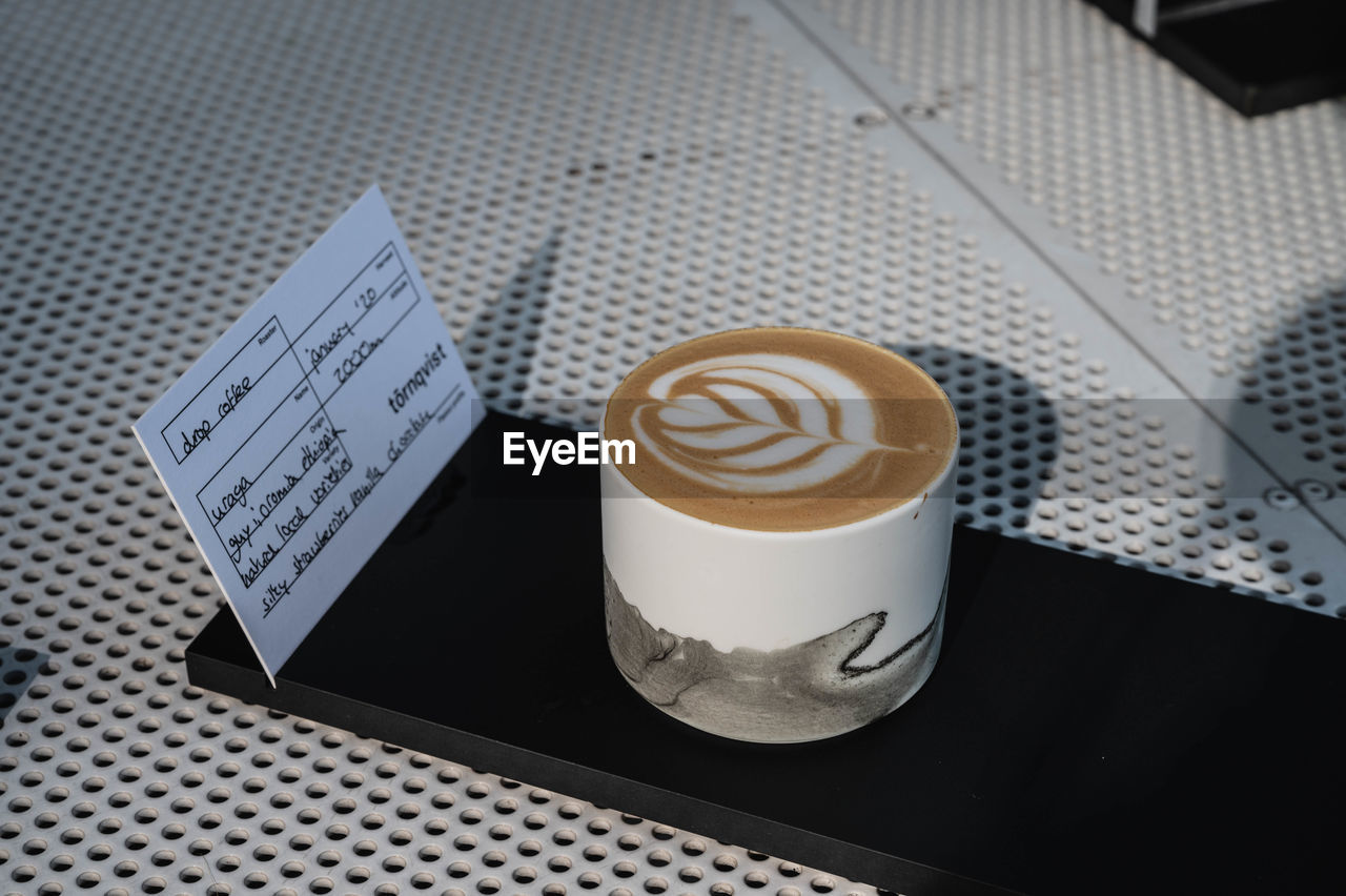 HIGH ANGLE VIEW OF COFFEE CUP ON TABLE WITH TEXT