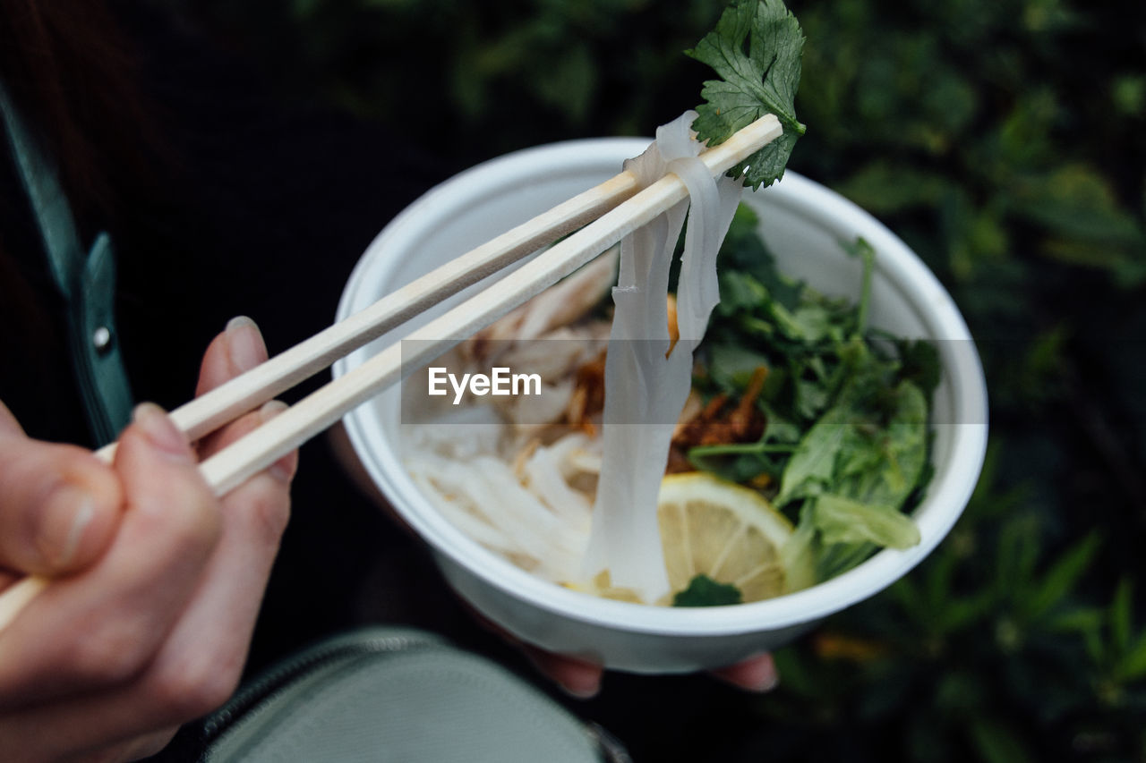 Cropped Hand Holding Noodles With Chopsticks
