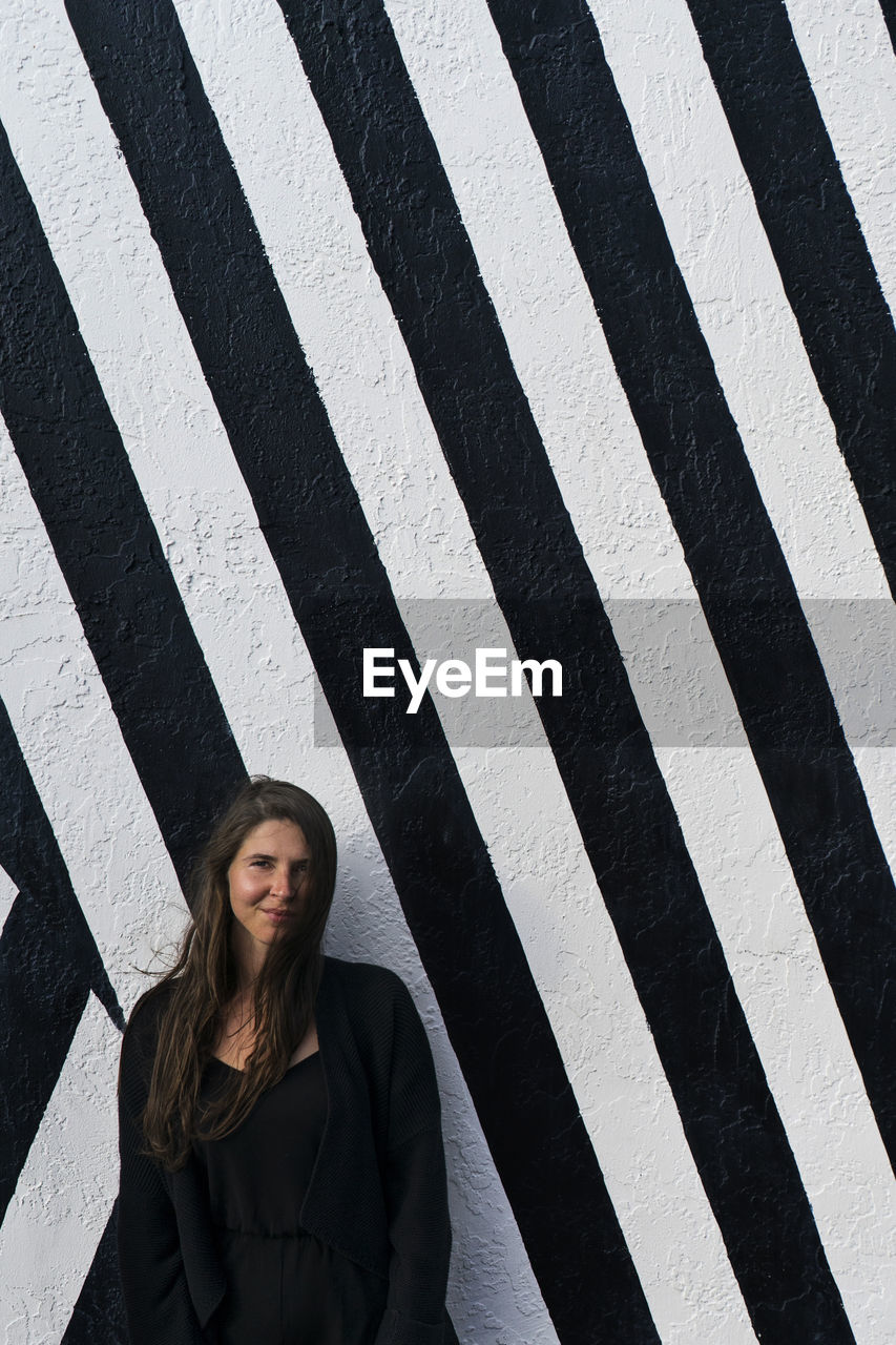 Portrait of woman standing against striped wall