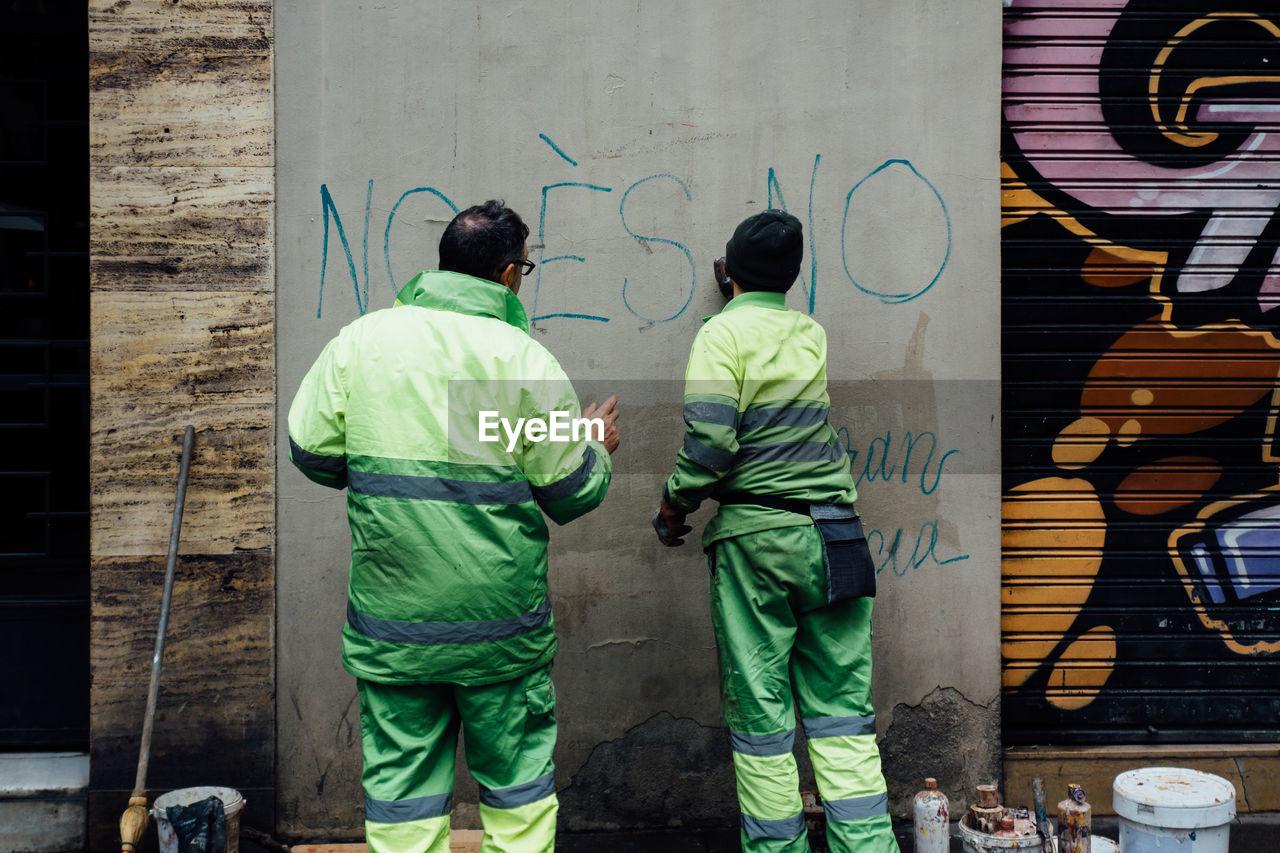 Rear View Of Men Making Graffiti On Concrete Wall