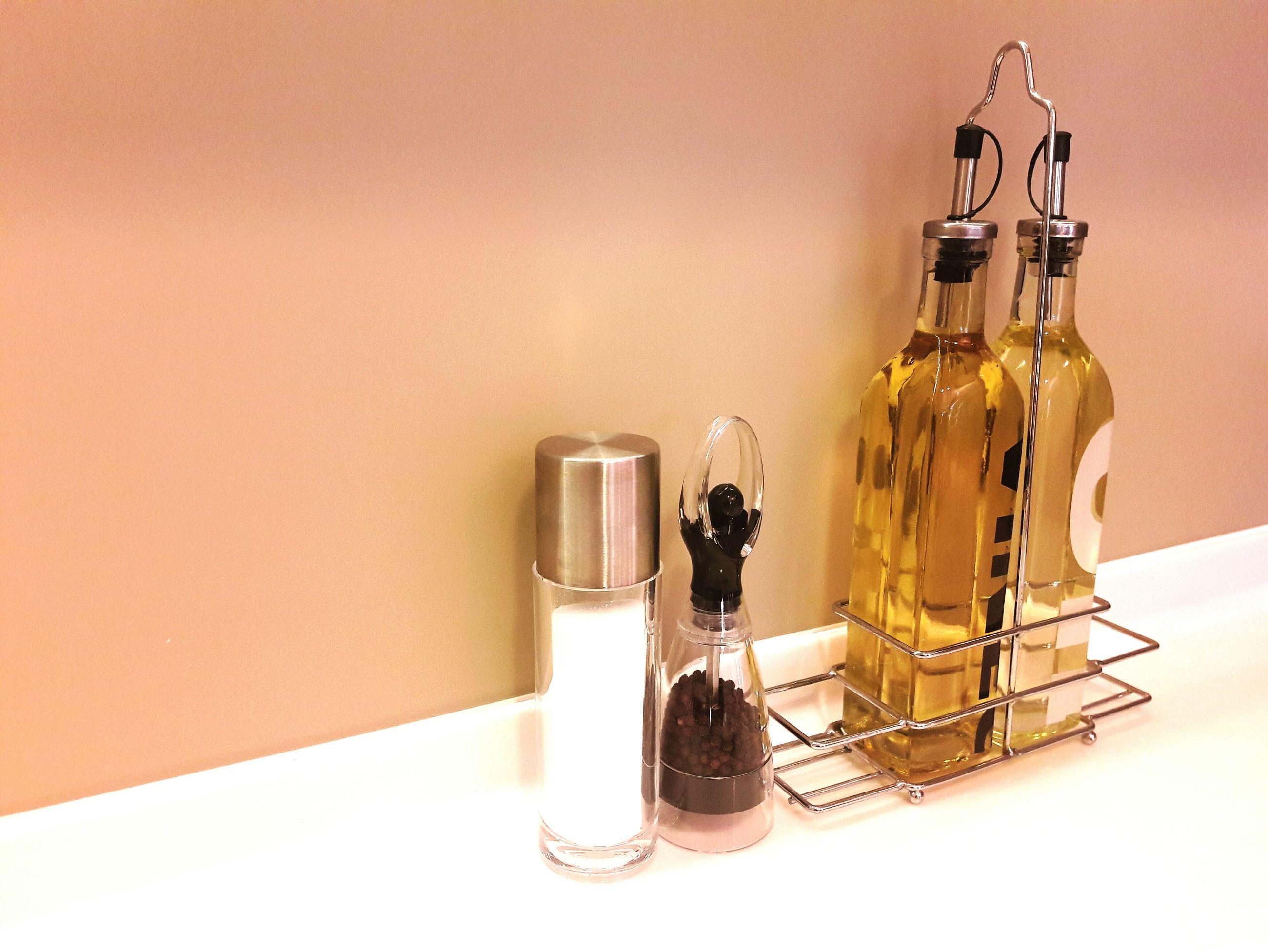 Olive oil in bottles by pepper and salt shaker on table