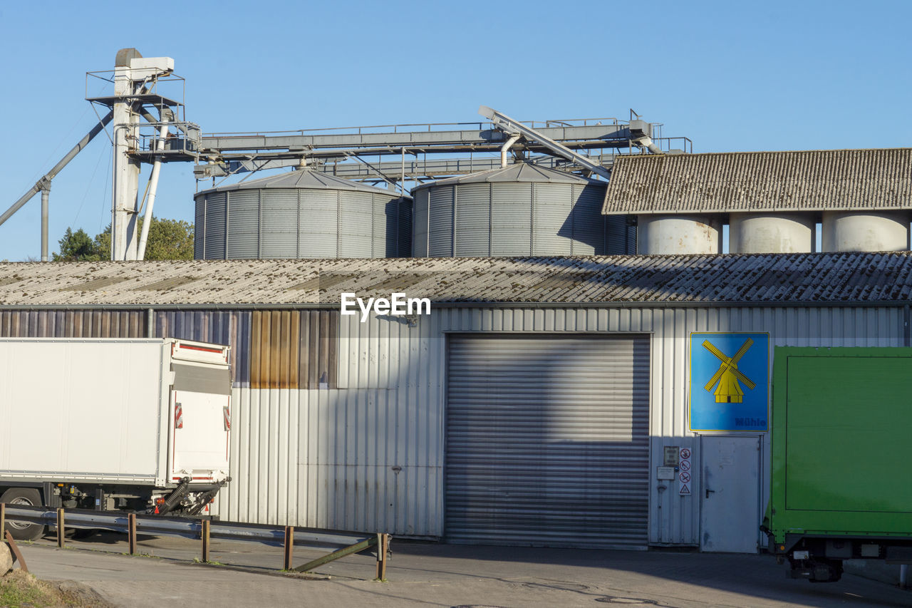 architecture, building exterior, built structure, sky, factory, day, industry, nature, sunlight, blue, clear sky, building, no people, outdoors, metal, industrial building, transportation, business, shadow, low angle view