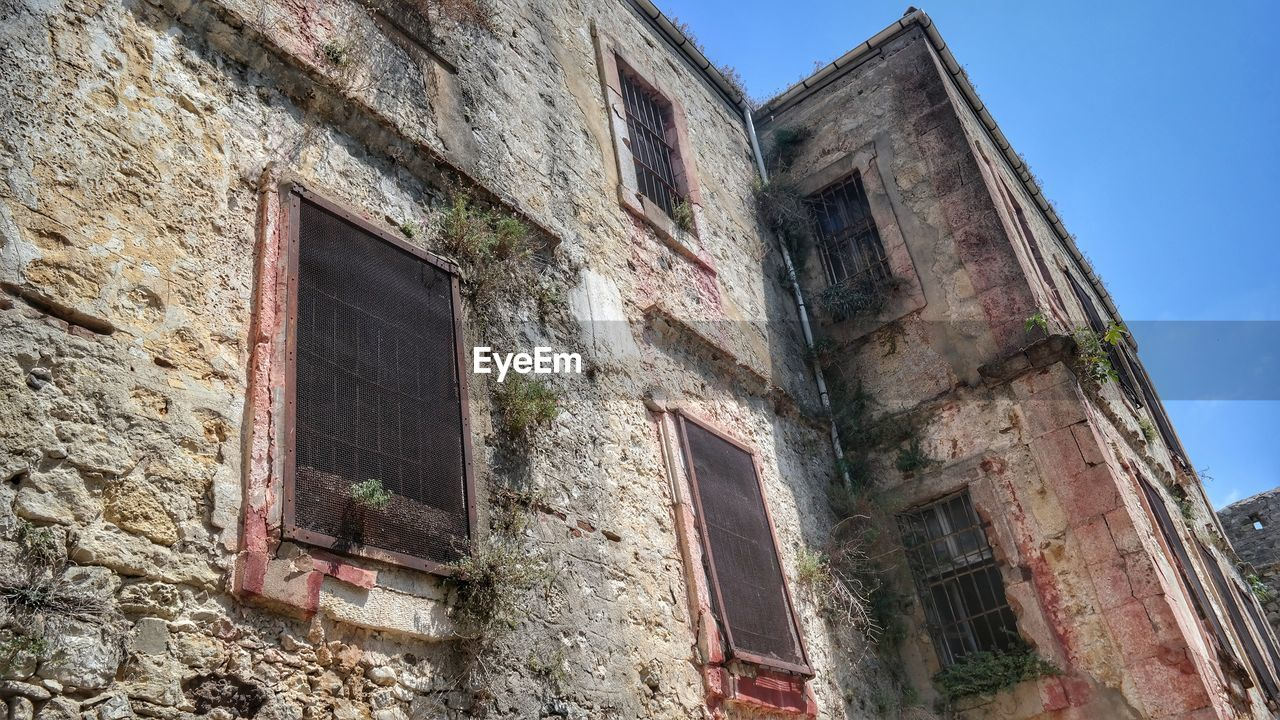 window, architecture, abandoned, low angle view, no people, building exterior, day, built structure, outdoors, sky, desolate