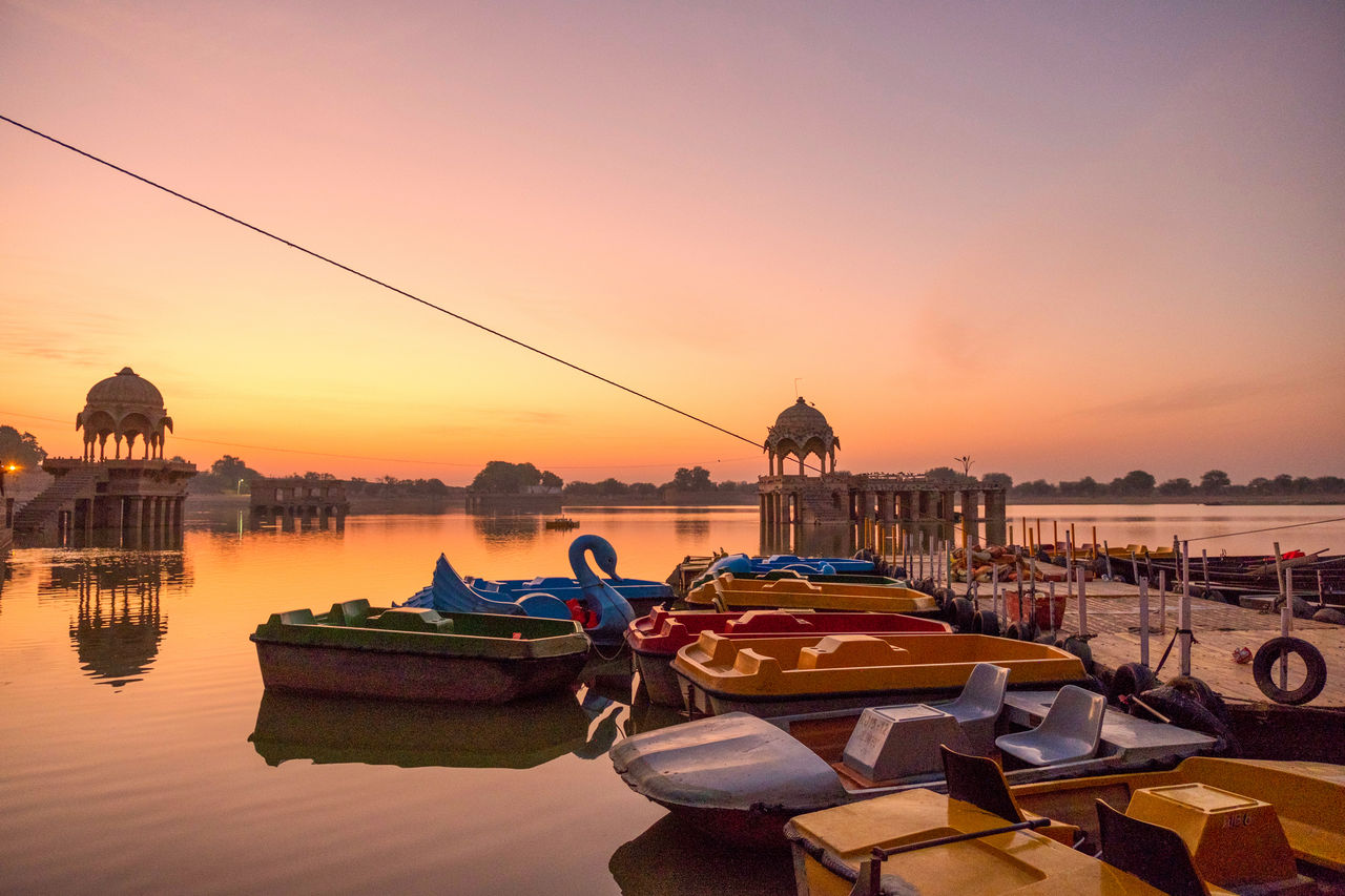Boats Moored In River During Sunset