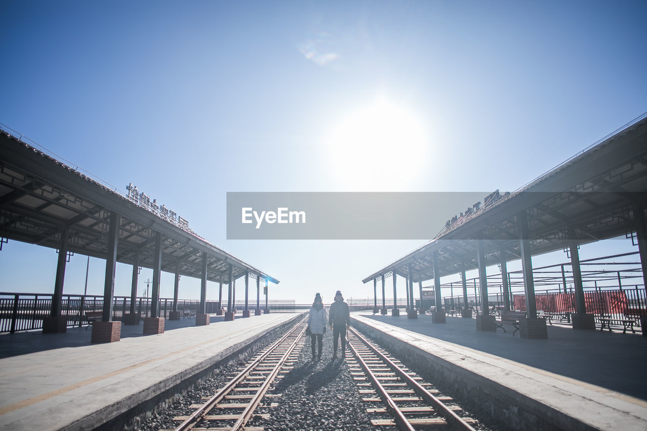 sky, rail transportation, sunlight, railroad track, track, architecture, transportation, sun, built structure, nature, real people, day, direction, sunny, the way forward, railroad station platform, clear sky, railroad station, diminishing perspective, outdoors, lens flare, bright