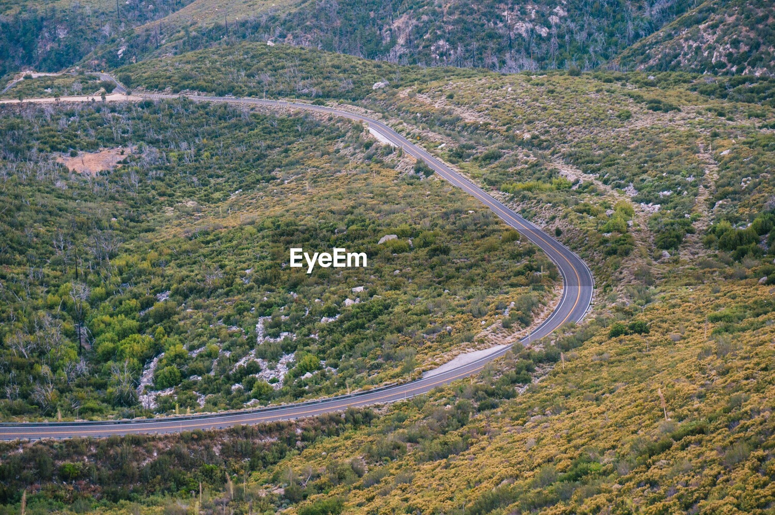 HIGH ANGLE VIEW OF ROAD PASSING THROUGH LANDSCAPE
