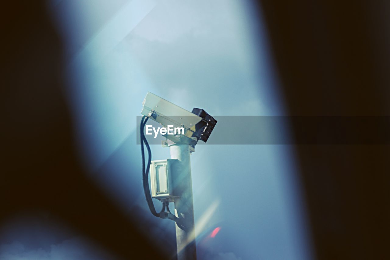 technology, indoors, surveillance, camera - photographic equipment, photography themes, security, no people, safety, security camera, close-up, low angle view, security system, photographic equipment, illuminated, selective focus, blue, modern, day, protection, equipment, digital camera