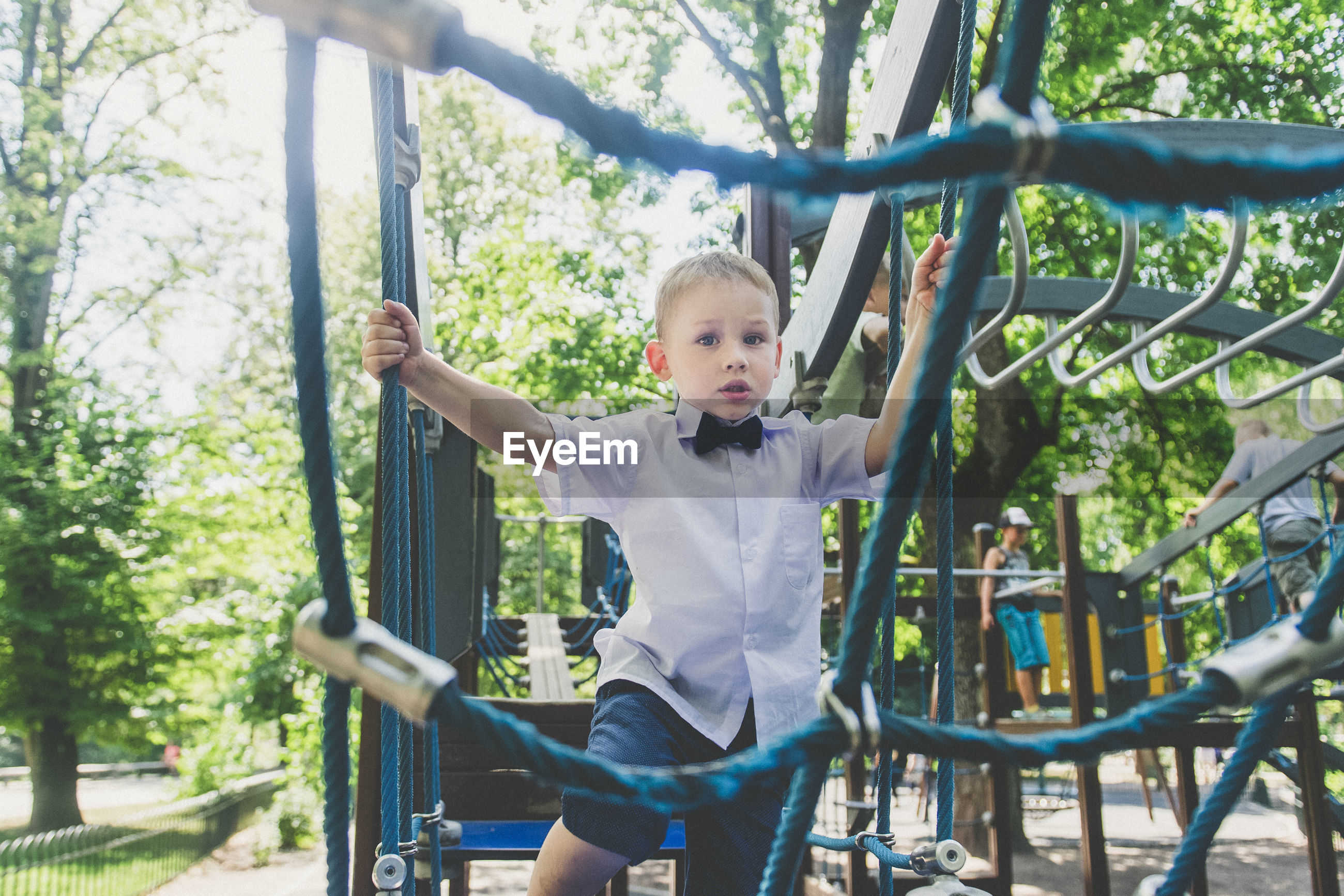 Portrait of boy climbing on rope at playground