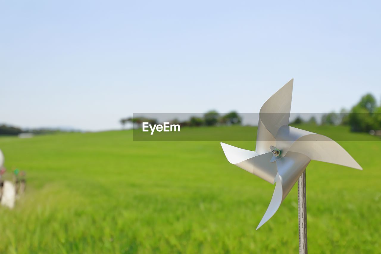 grass, sky, nature, field, land, focus on foreground, no people, day, plant, copy space, creativity, outdoors, green color, close-up, environment, clear sky, toy, art and craft, paper, blue