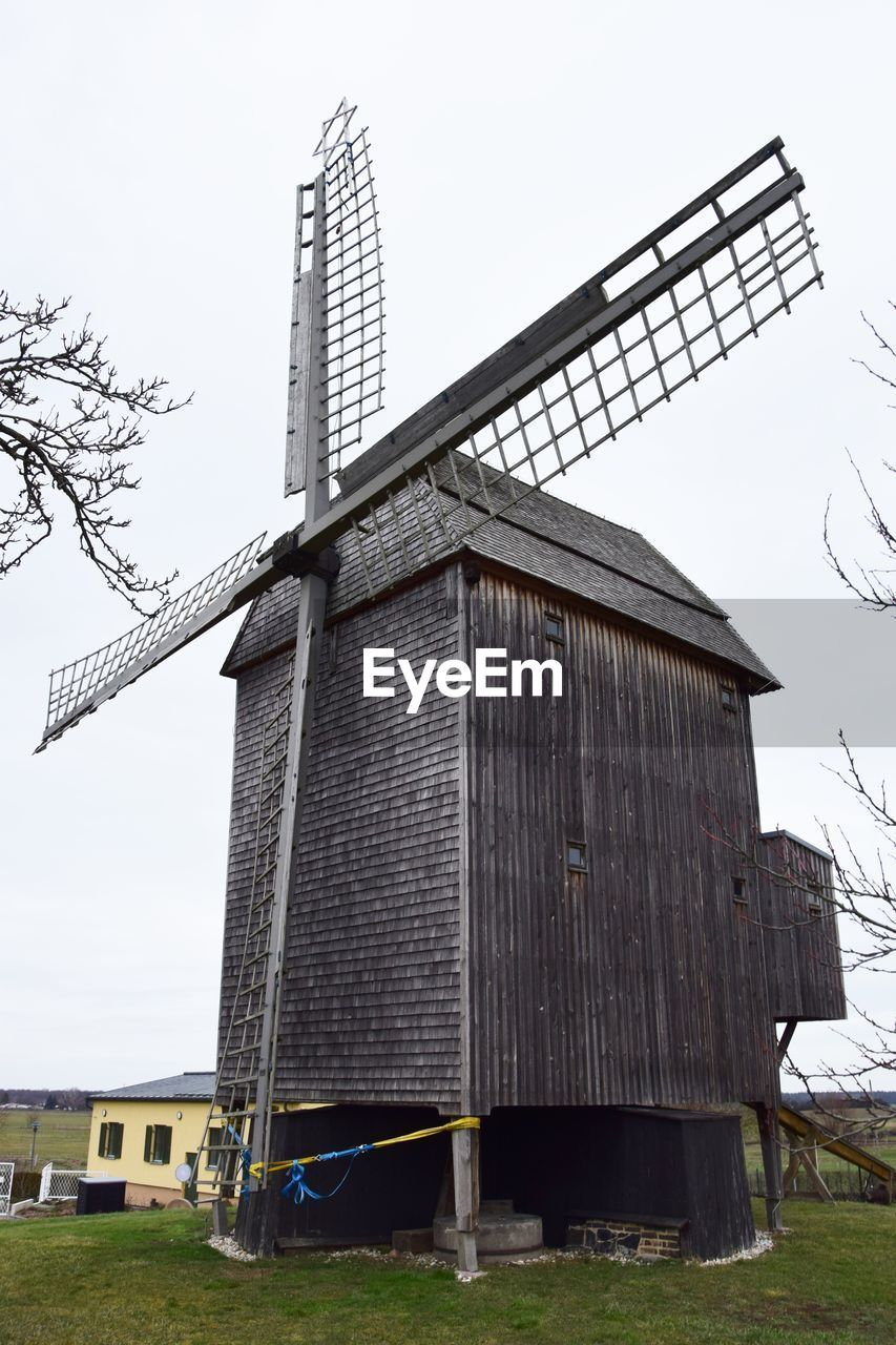architecture, built structure, building exterior, renewable energy, wind power, sky, environmental conservation, turbine, alternative energy, wind turbine, field, environment, traditional windmill, fuel and power generation, nature, day, rural scene, landscape, no people, land, outdoors