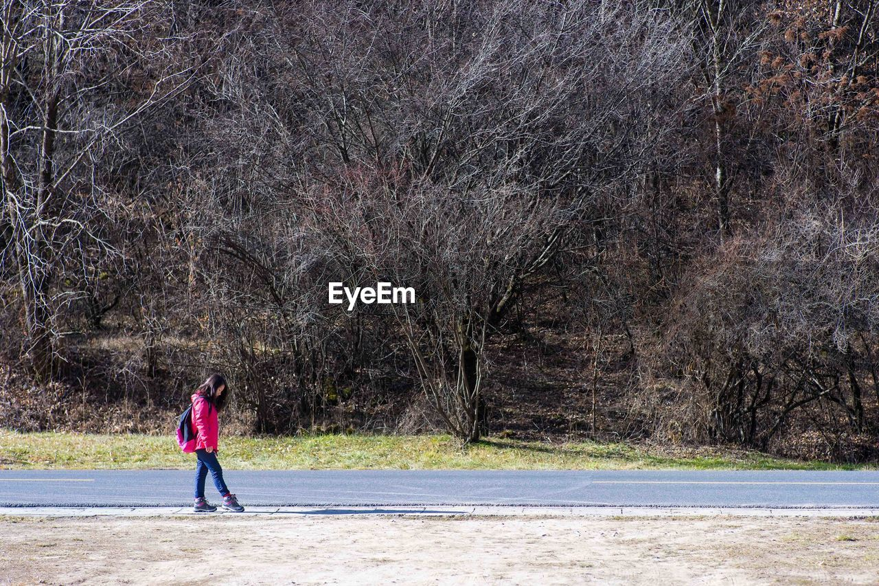 Side View Of Girl With Backpack Walking On Road Amidst Bare Trees