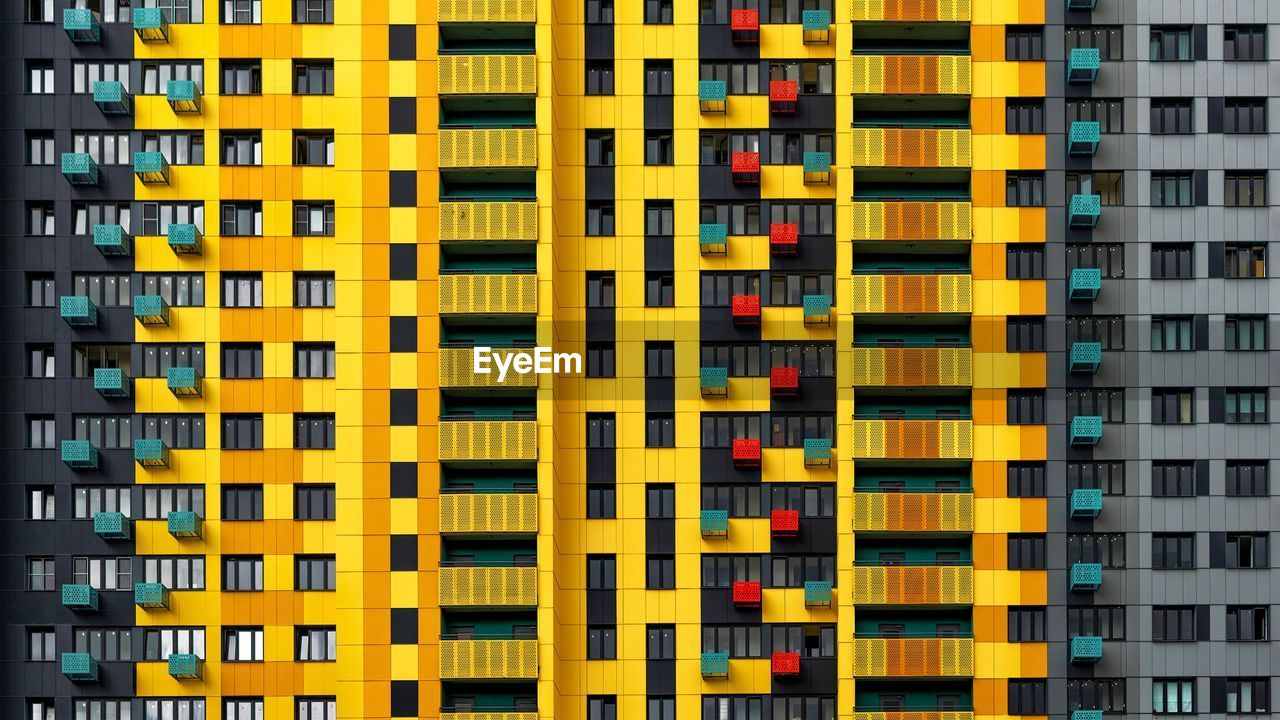 yellow, built structure, architecture, building exterior, full frame, no people, building, multi colored, backgrounds, repetition, city, modern, in a row, pattern, window, outdoors, residential district, side by side, day, apartment