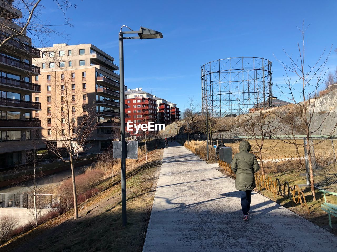 Rear view of woman walking on footpath in city against sky