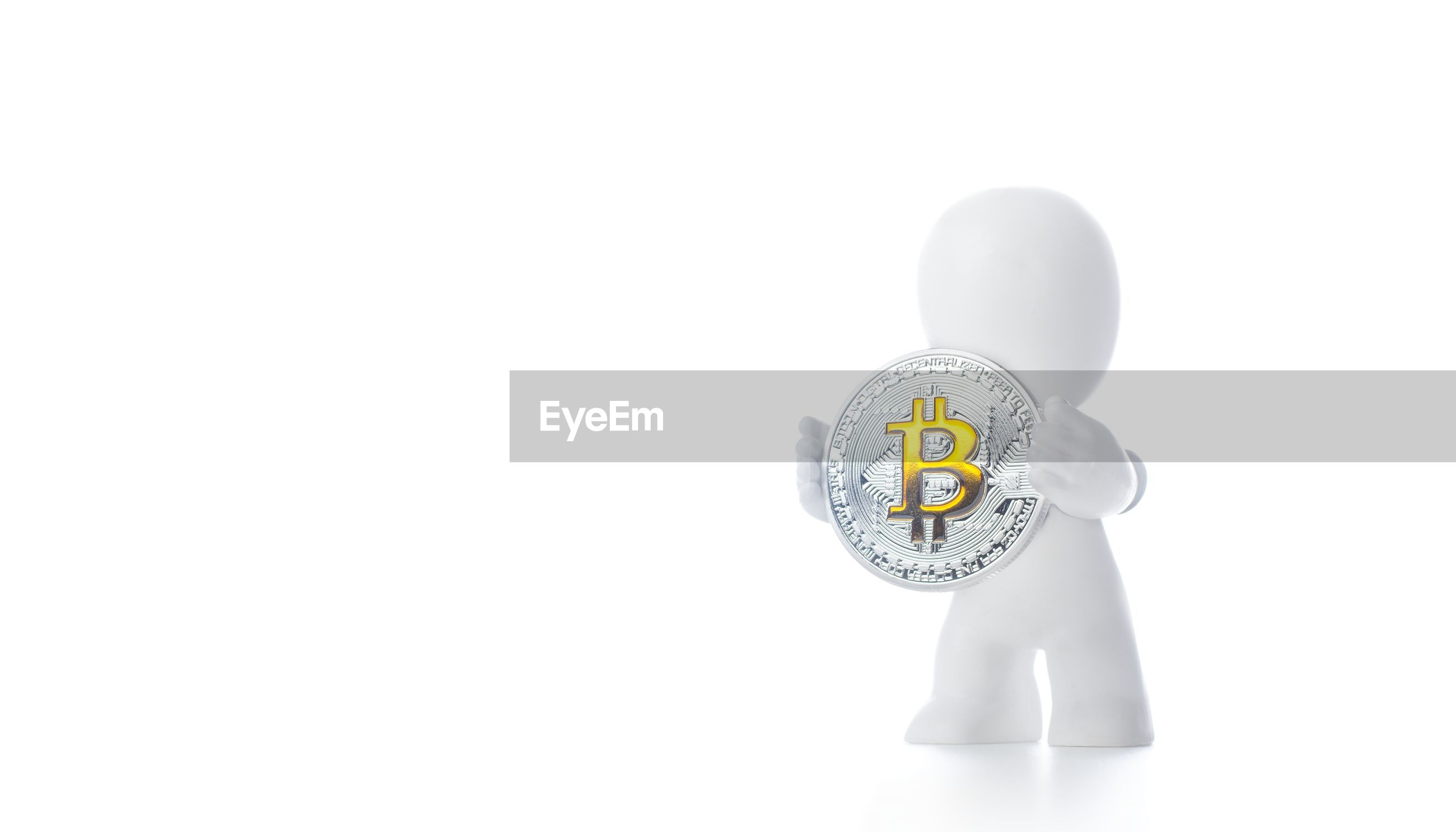 Close-up of figurine with bitcoin against white background