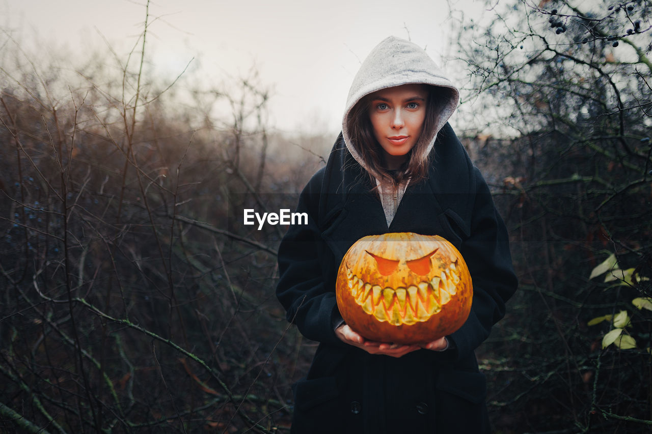 Portrait Of Woman Holding Pumpkin In Forest During Autumn