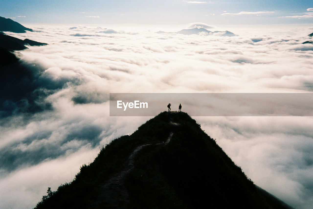 People Standing On Mountain Against Cloudscape