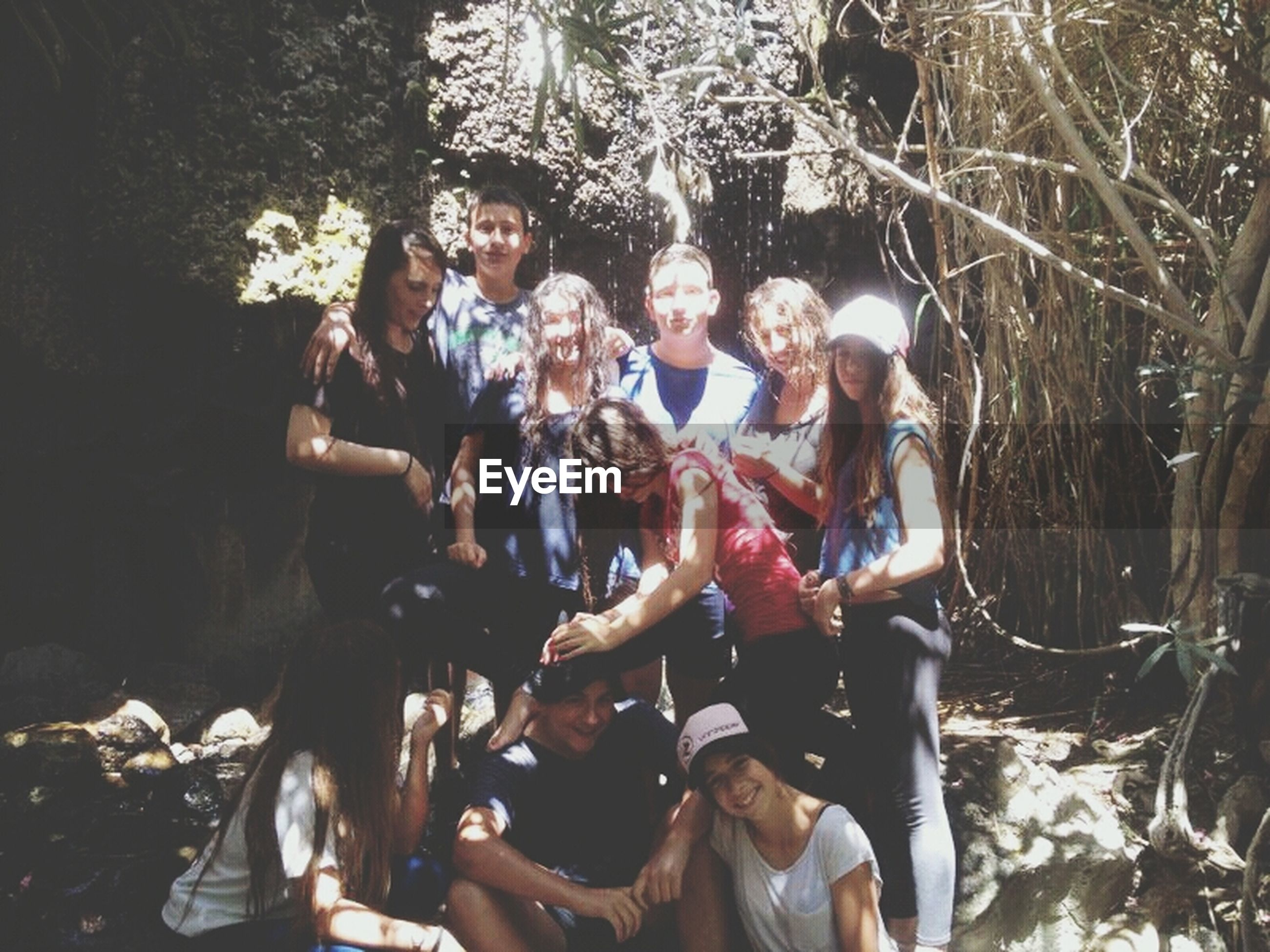lifestyles, leisure activity, togetherness, tree, men, casual clothing, enjoyment, person, fun, full length, sitting, friendship, outdoors, holding, celebration, happiness, day