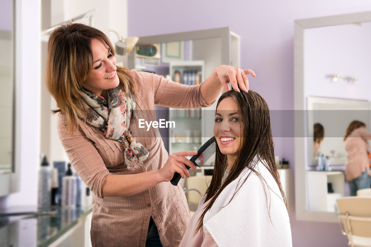 women, indoors, customer, focus on foreground, real people, beauty, young women, people, adult, hairdresser, waist up, two people, hairstyle, smiling, lifestyles, young adult, holding, hair, occupation, beautiful woman, beautician, human hair, combing