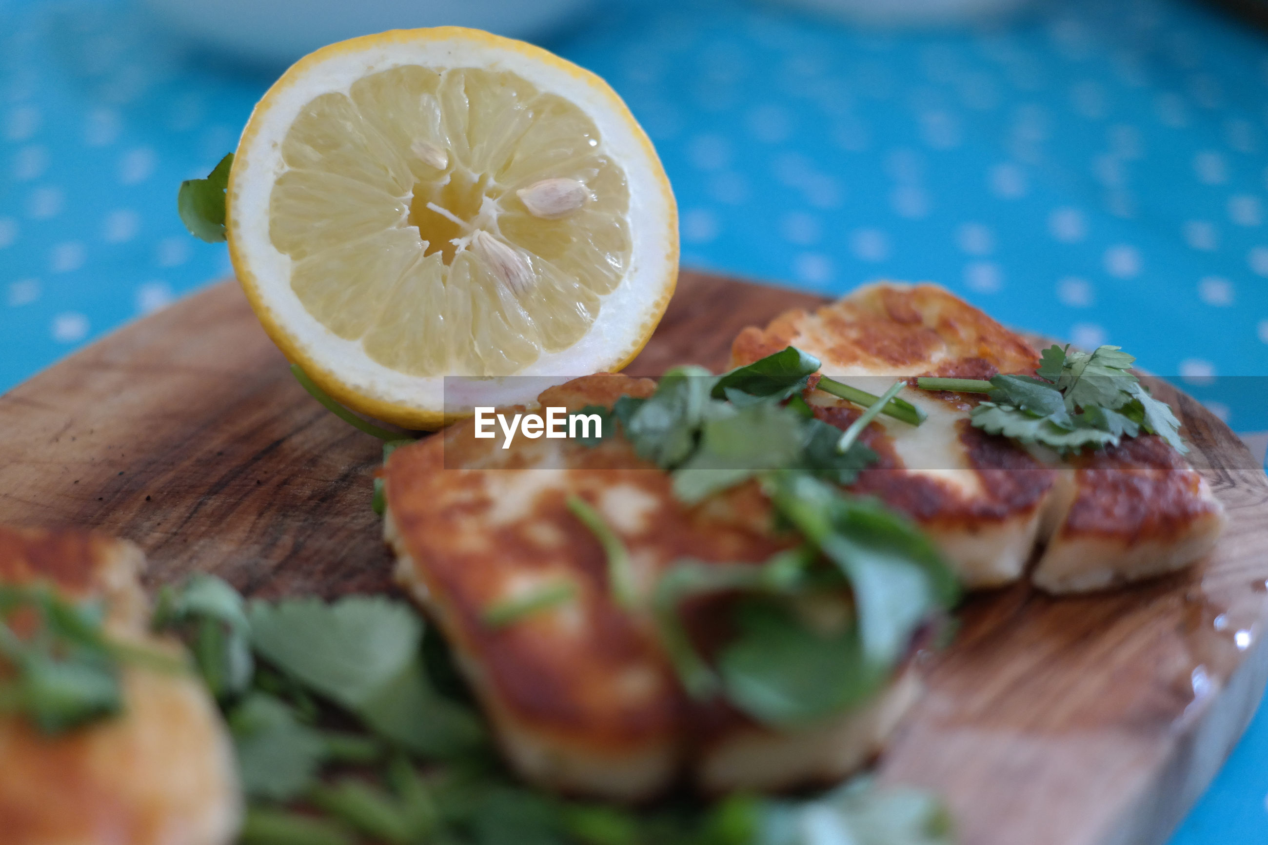 Close-up of halloumi with lemon on cutting board