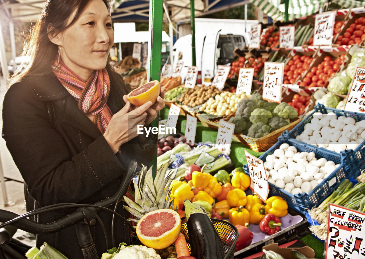 MIDSECTION OF WOMAN WITH FRUITS IN STORE