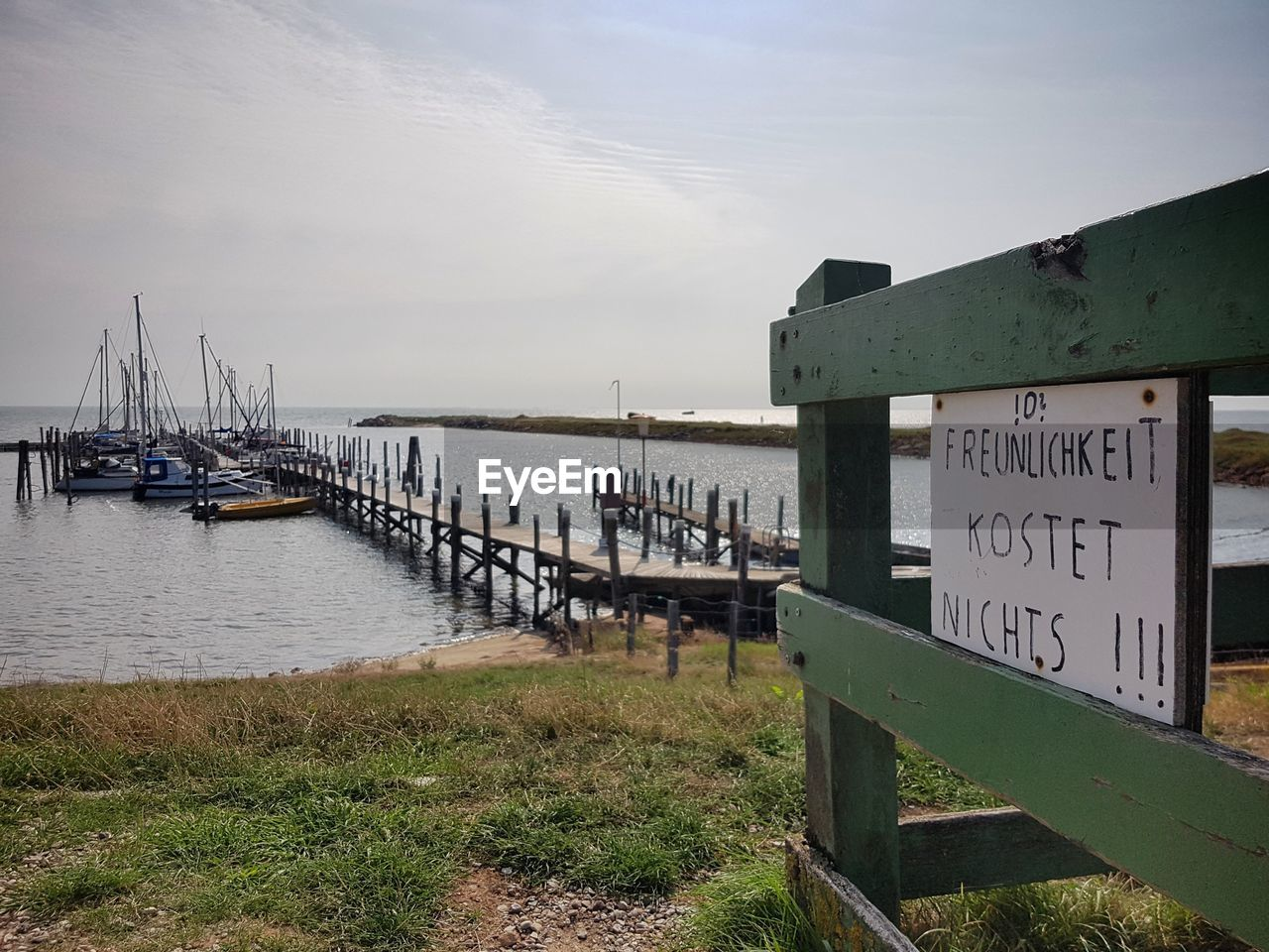water, sky, communication, nature, text, sign, nautical vessel, day, land, transportation, no people, western script, sea, pier, wood - material, architecture, beach, information, built structure, outdoors