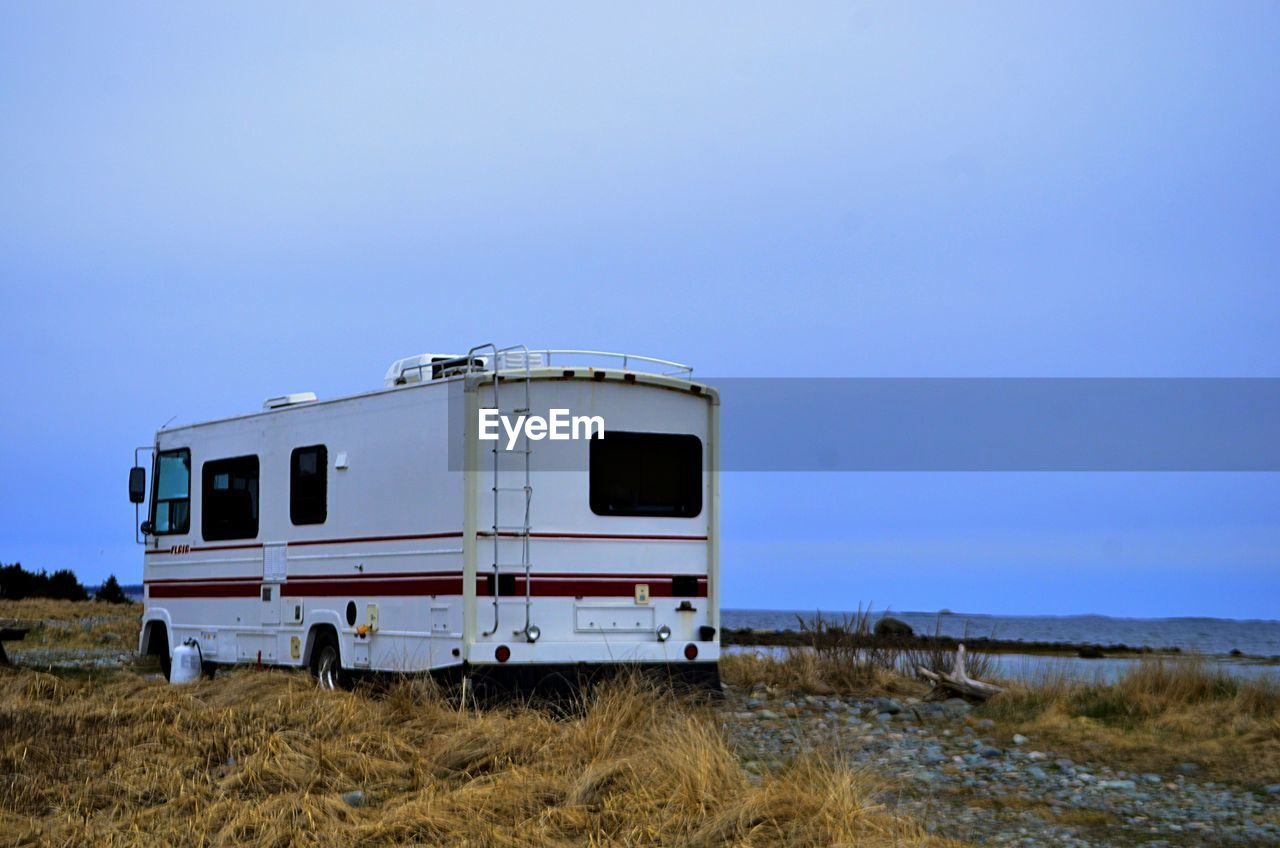 View Of Parked Caravan Against Landscape And Clear Blue Sky