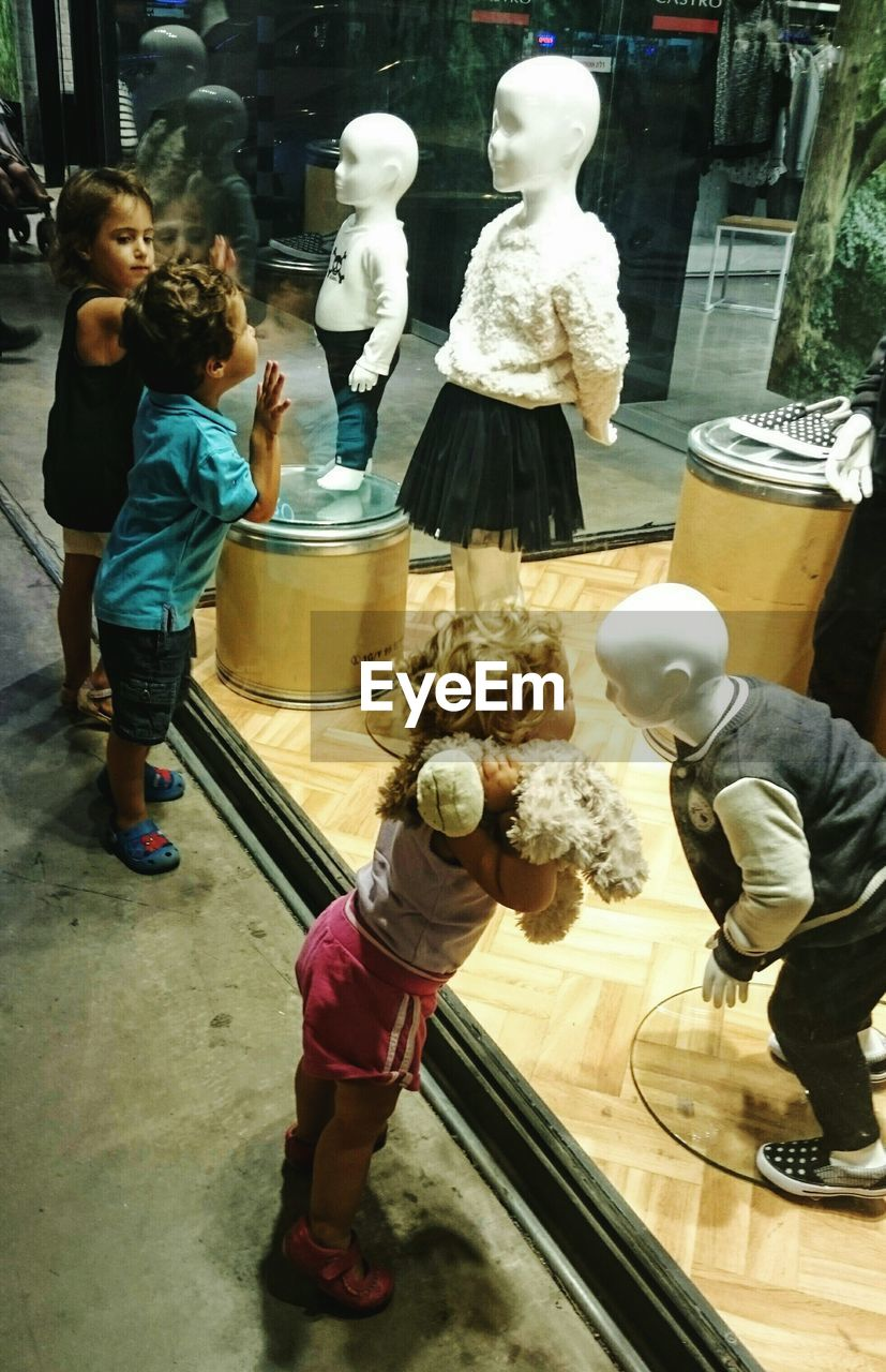 High Angle View Of Children Looking At Mannequins In Store