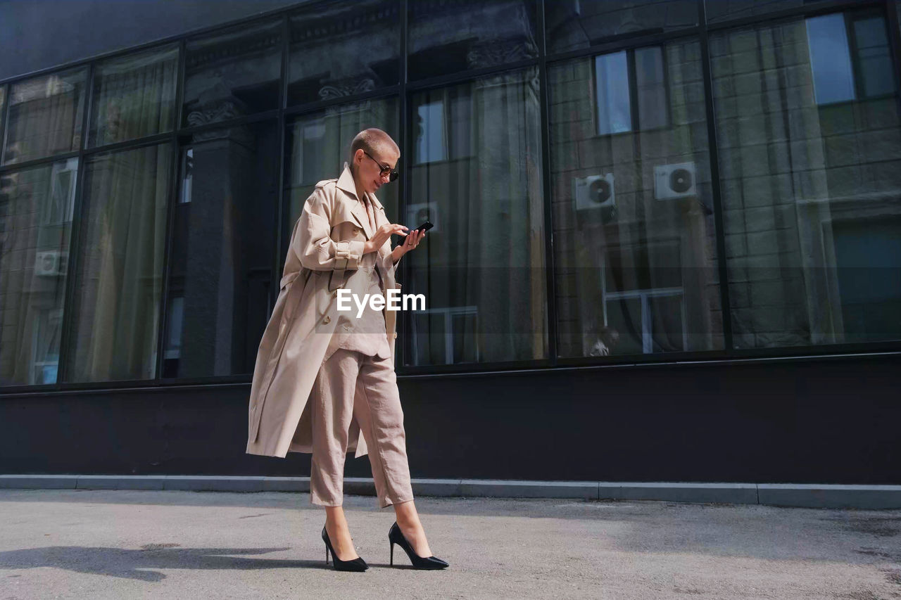 Full length of businesswoman using mobile while standing against building