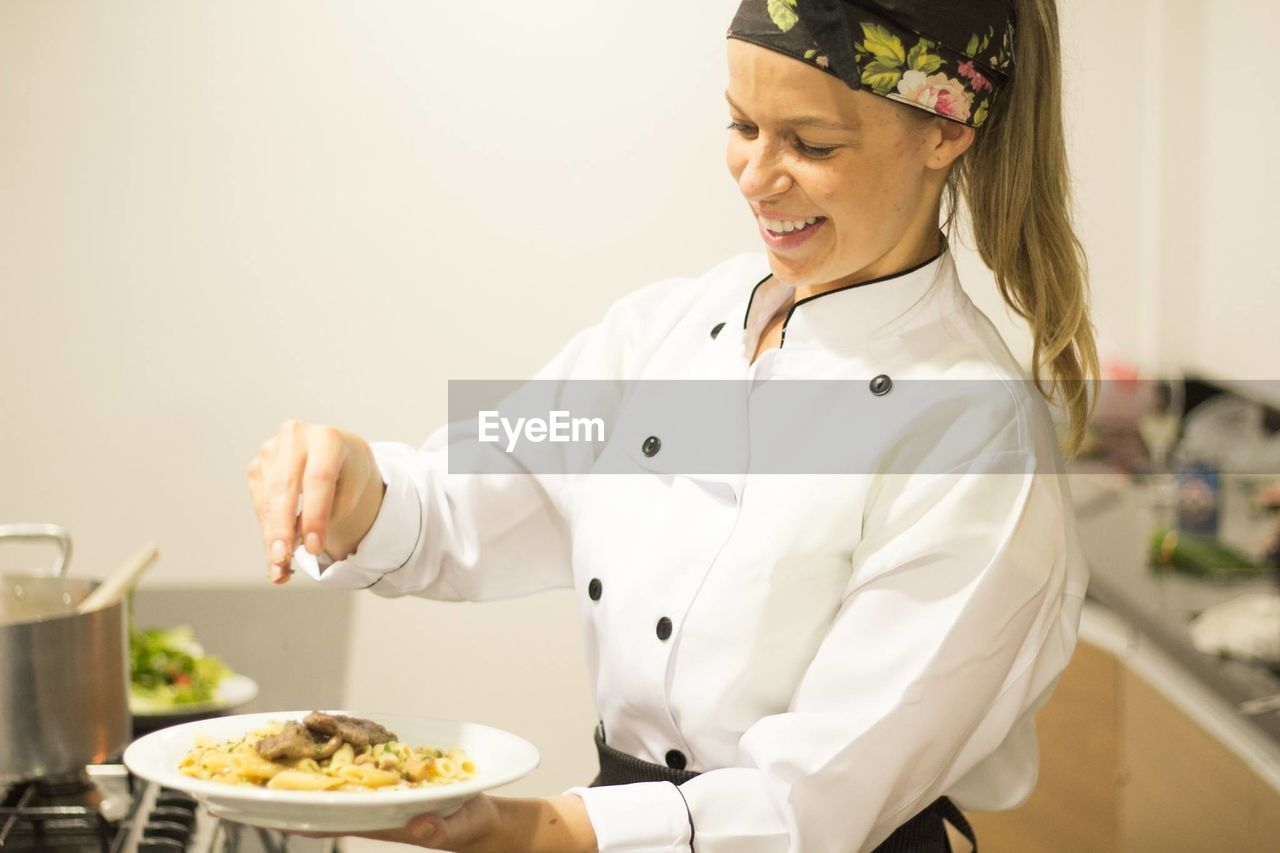 Happy female chef garnishing pasta in plate at commercial kitchen