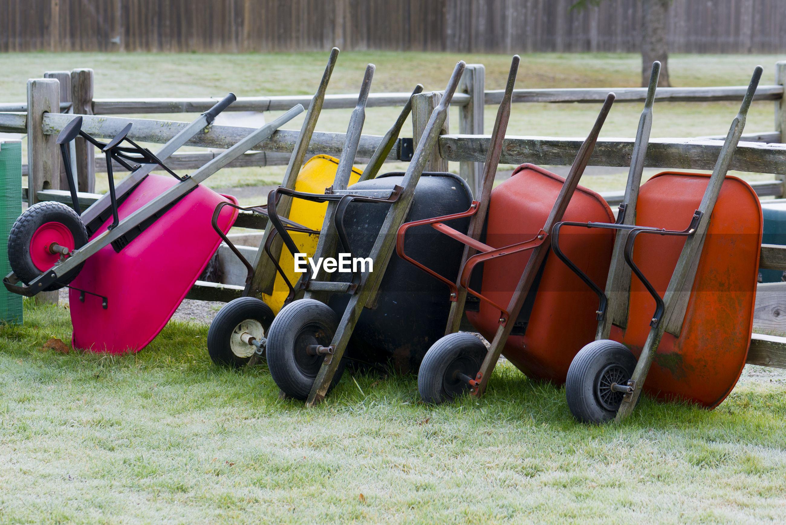 Colorful wheelbarrows on grassy field