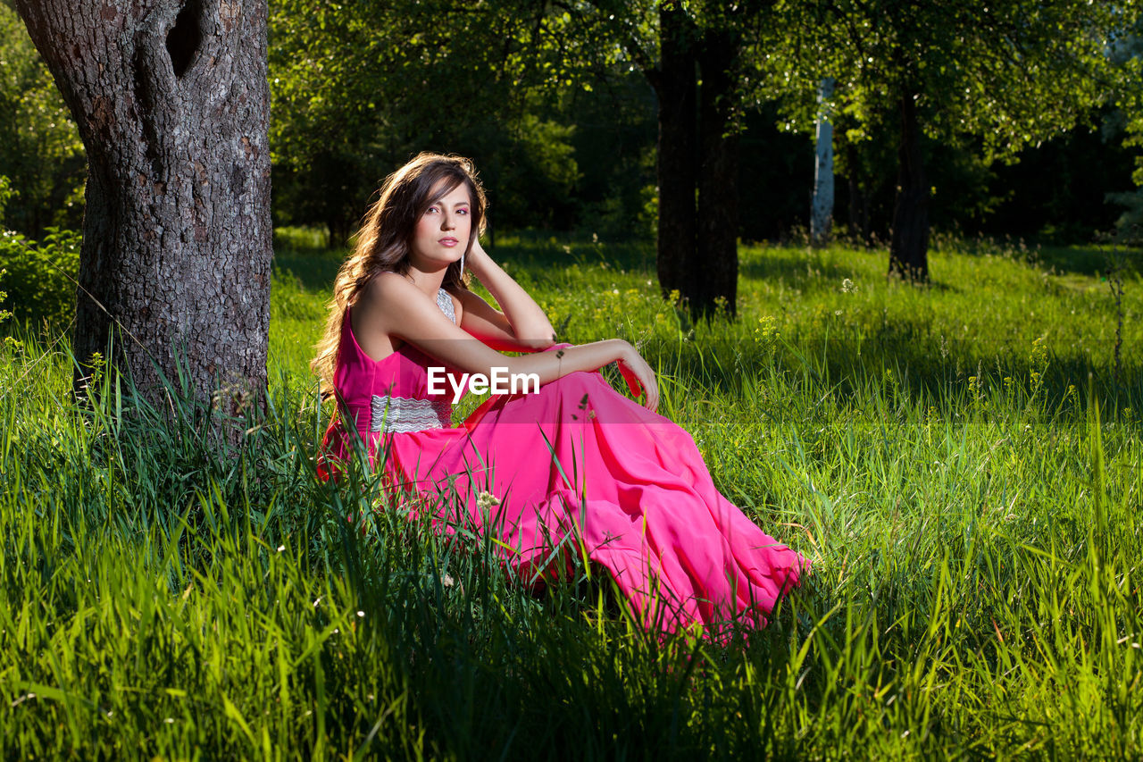 plant, one person, grass, real people, tree, leisure activity, full length, sitting, fashion, lifestyles, field, green color, land, dress, women, nature, young adult, three quarter length, day, pink color, contemplation, hairstyle, outdoors, beautiful woman