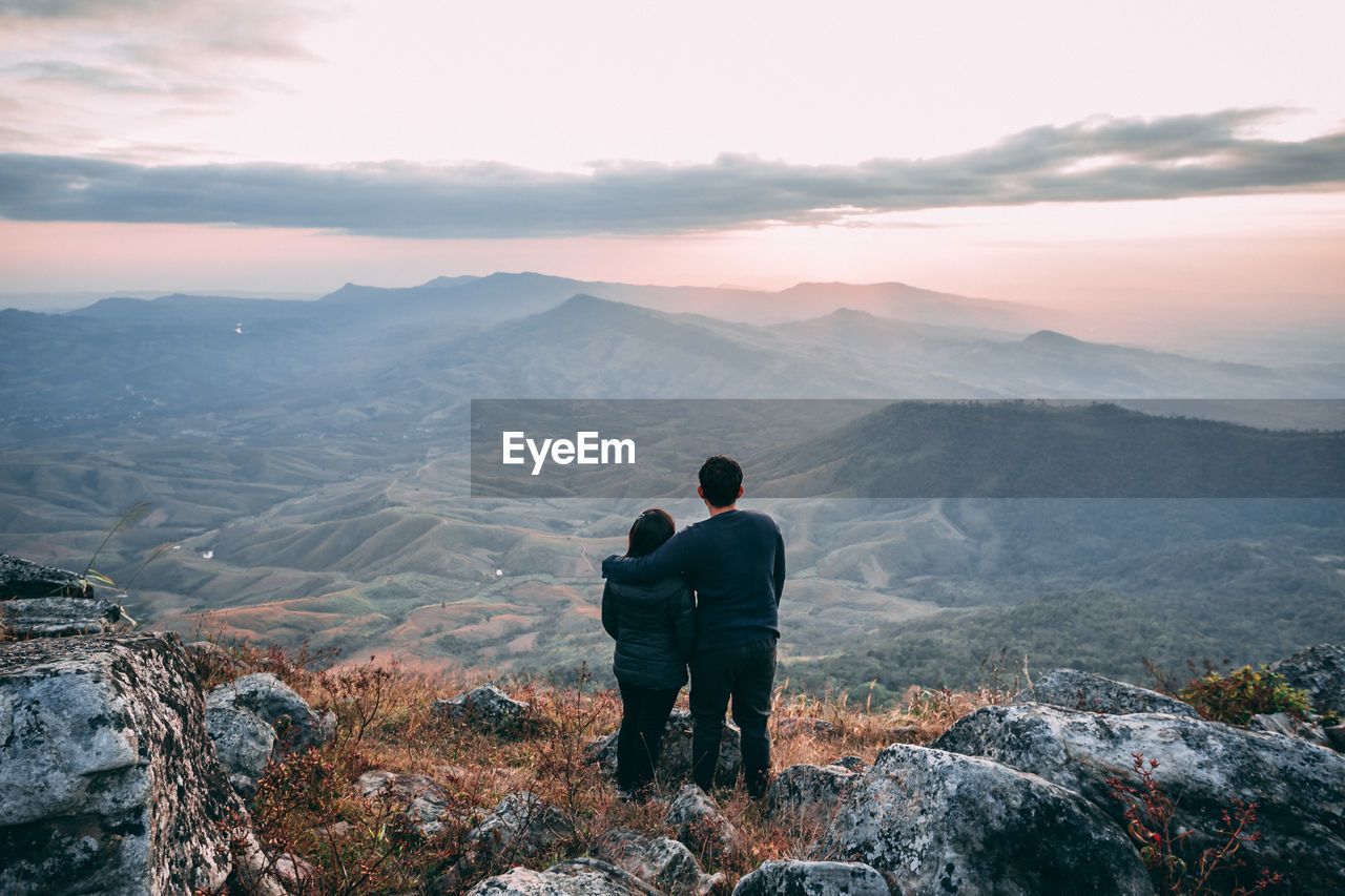 Rear View Of Couple Looking At Mountains Against Sky During Sunset