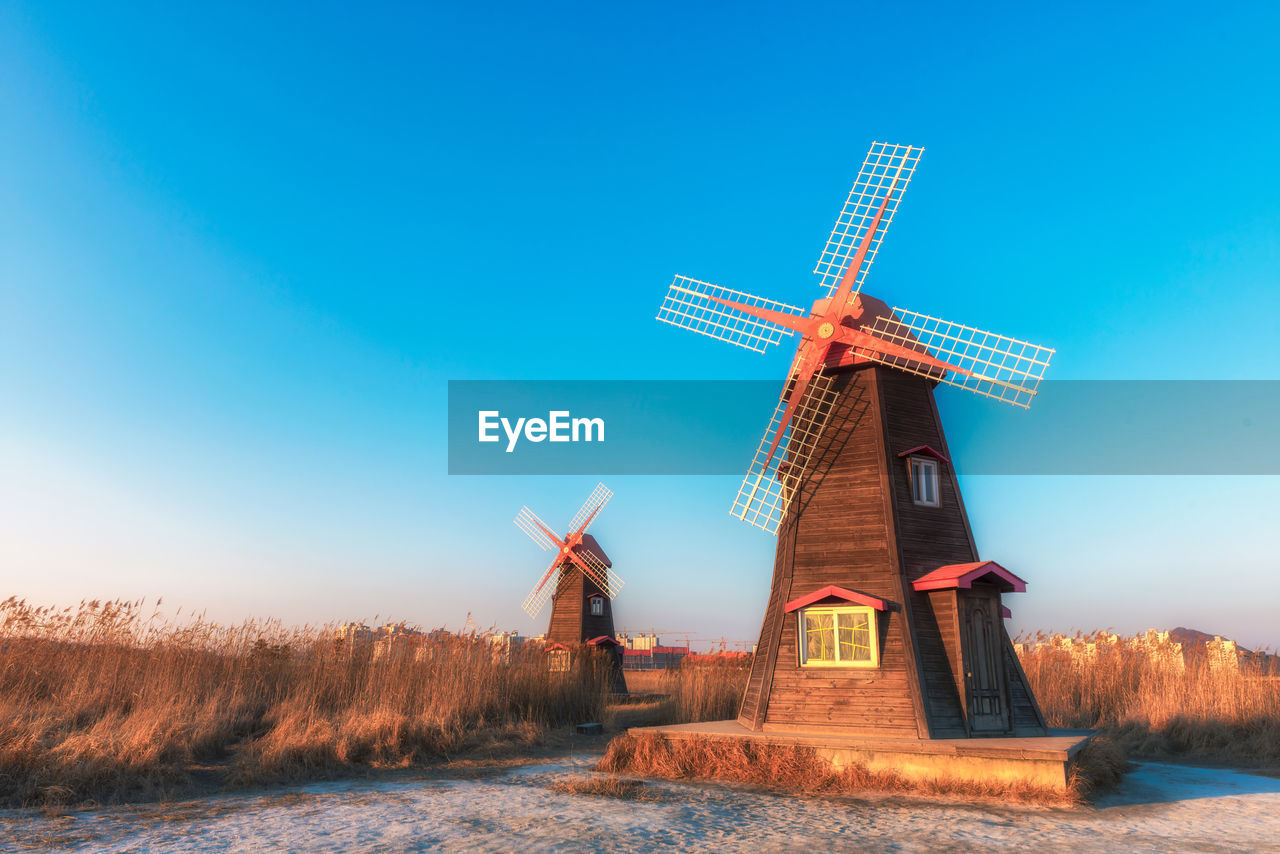 alternative energy, wind power, windmill, wind turbine, renewable energy, environmental conservation, fuel and power generation, traditional windmill, field, rural scene, nature, built structure, industrial windmill, outdoors, day, blue, architecture, no people, beauty in nature, sky, landscape, technology, clear sky, building exterior, scenics