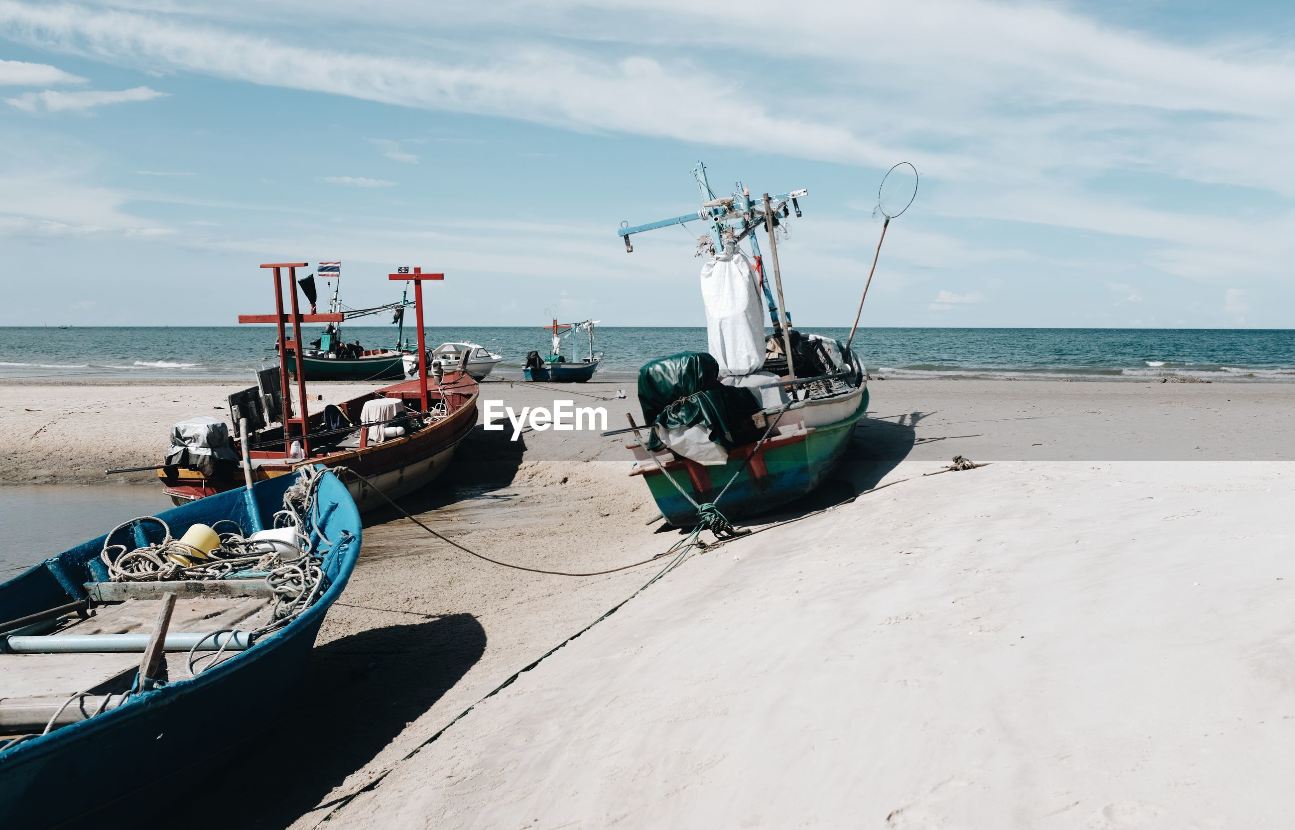FISHING BOATS ON BEACH AGAINST SKY