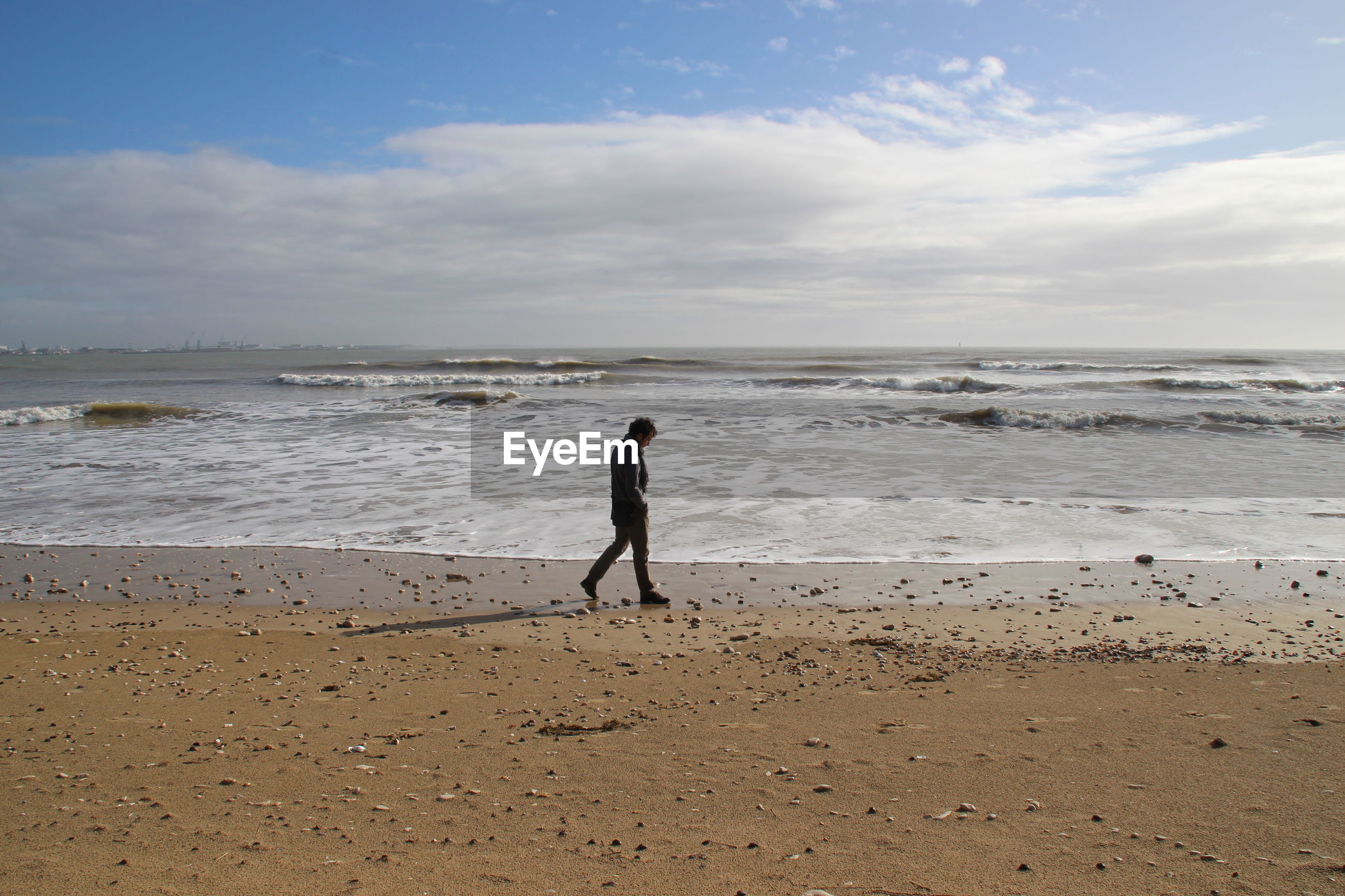 Side view of man walking at beach against sky