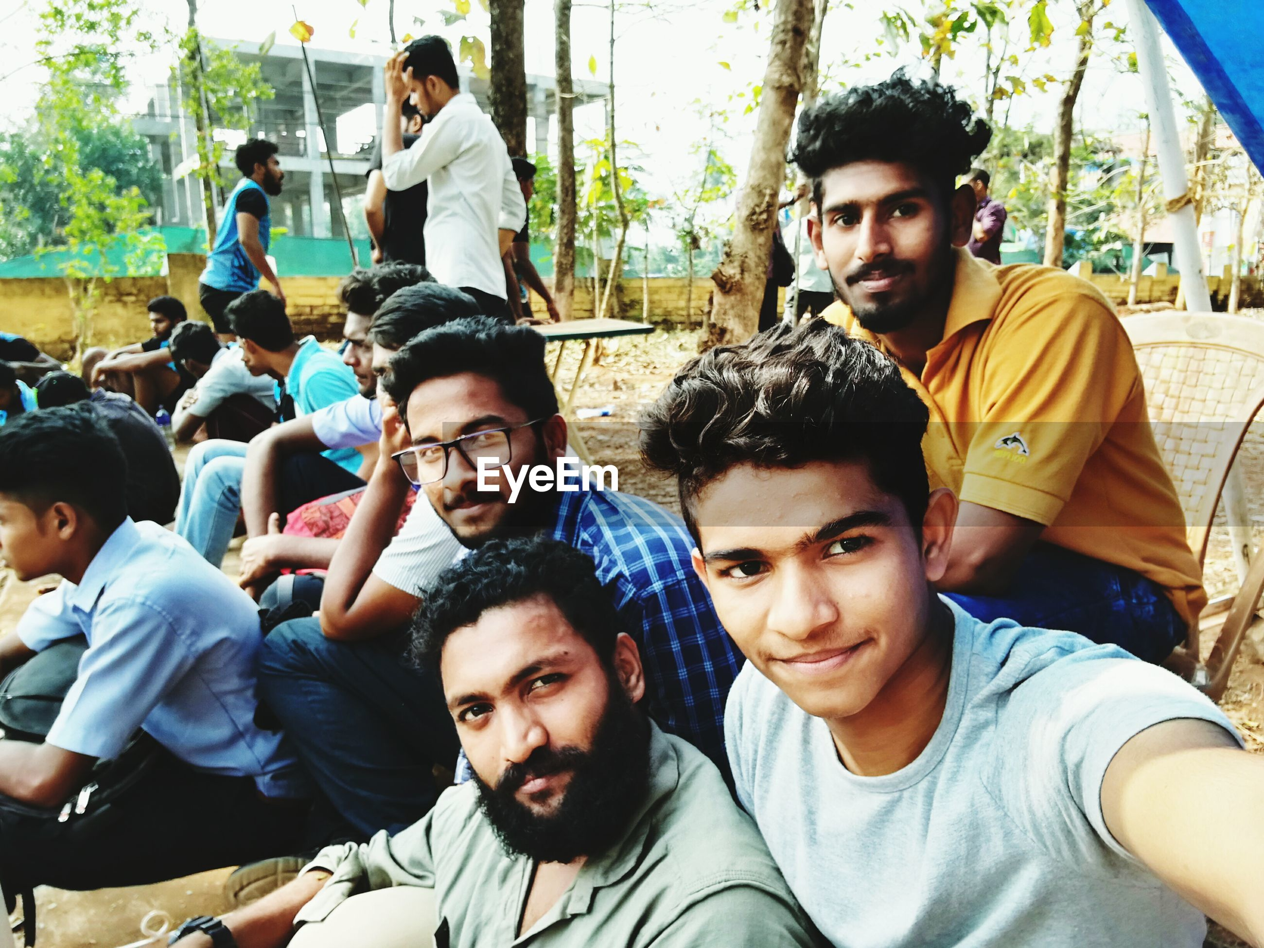 young adult, young men, friendship, young women, togetherness, real people, fun, beard, lifestyles, portrait, adult, people, tree, standing out from the crowd, adults only, men, outdoors, large group of people, human body part, crowd, day