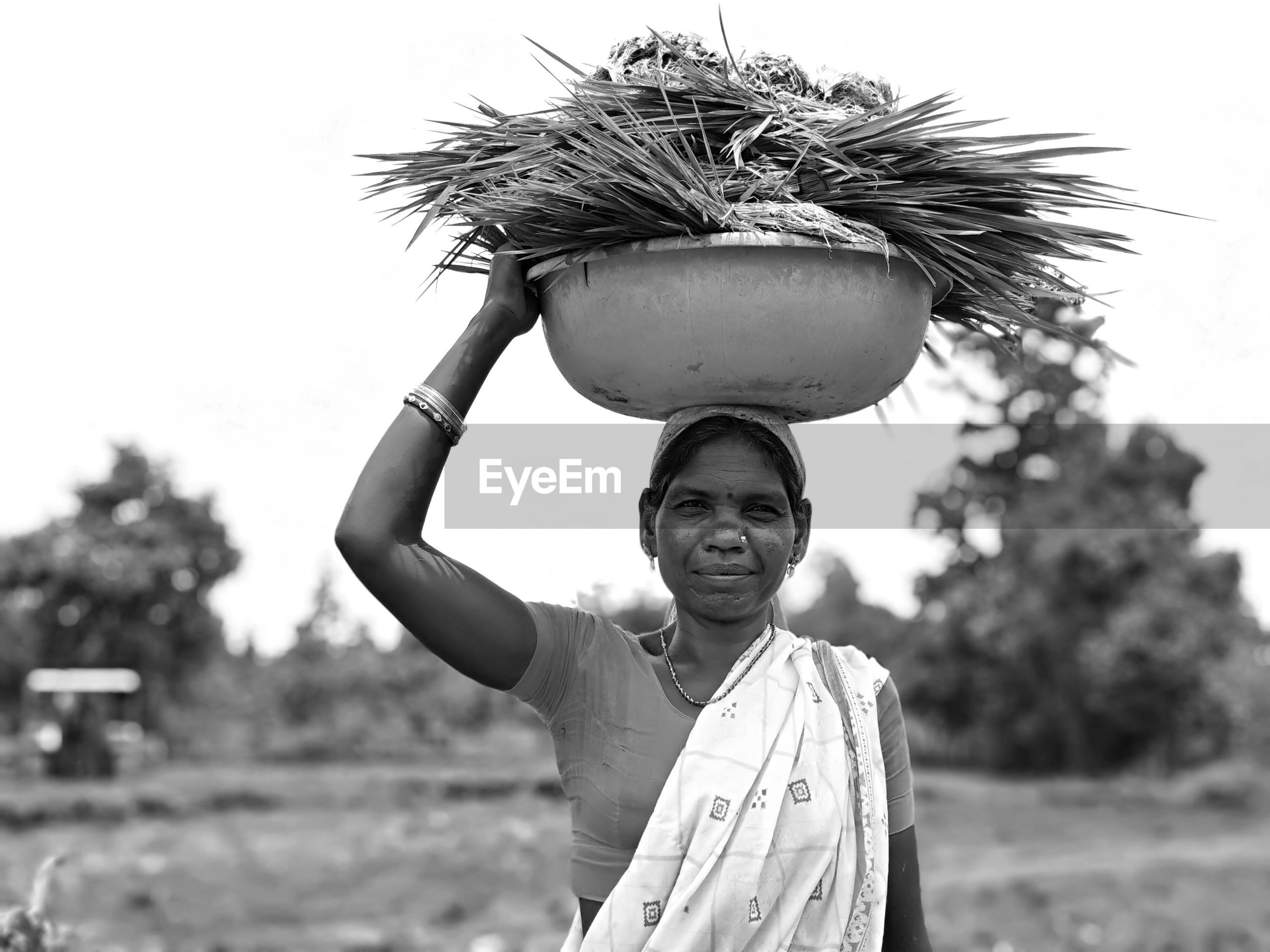 Portrait of smiling woman carrying basket on head