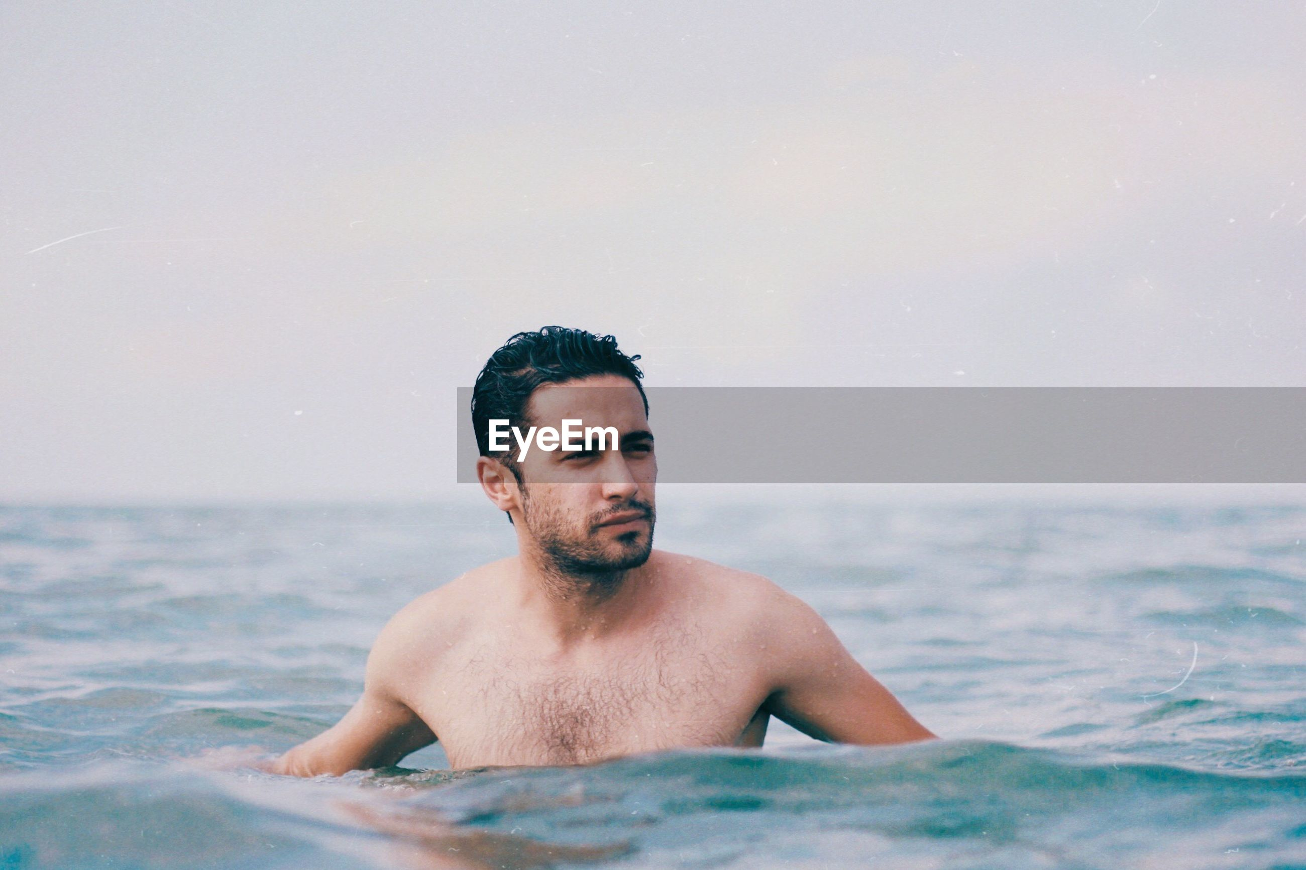 Shirtless young man looking away while swimming in sea against sky