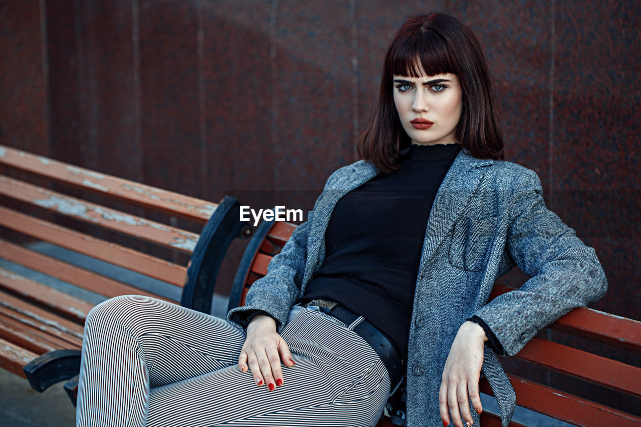sitting, one person, looking at camera, young adult, three quarter length, real people, women, young women, portrait, leisure activity, seat, adult, bench, front view, lifestyles, focus on foreground, beauty, beautiful woman, hairstyle, hair, bangs