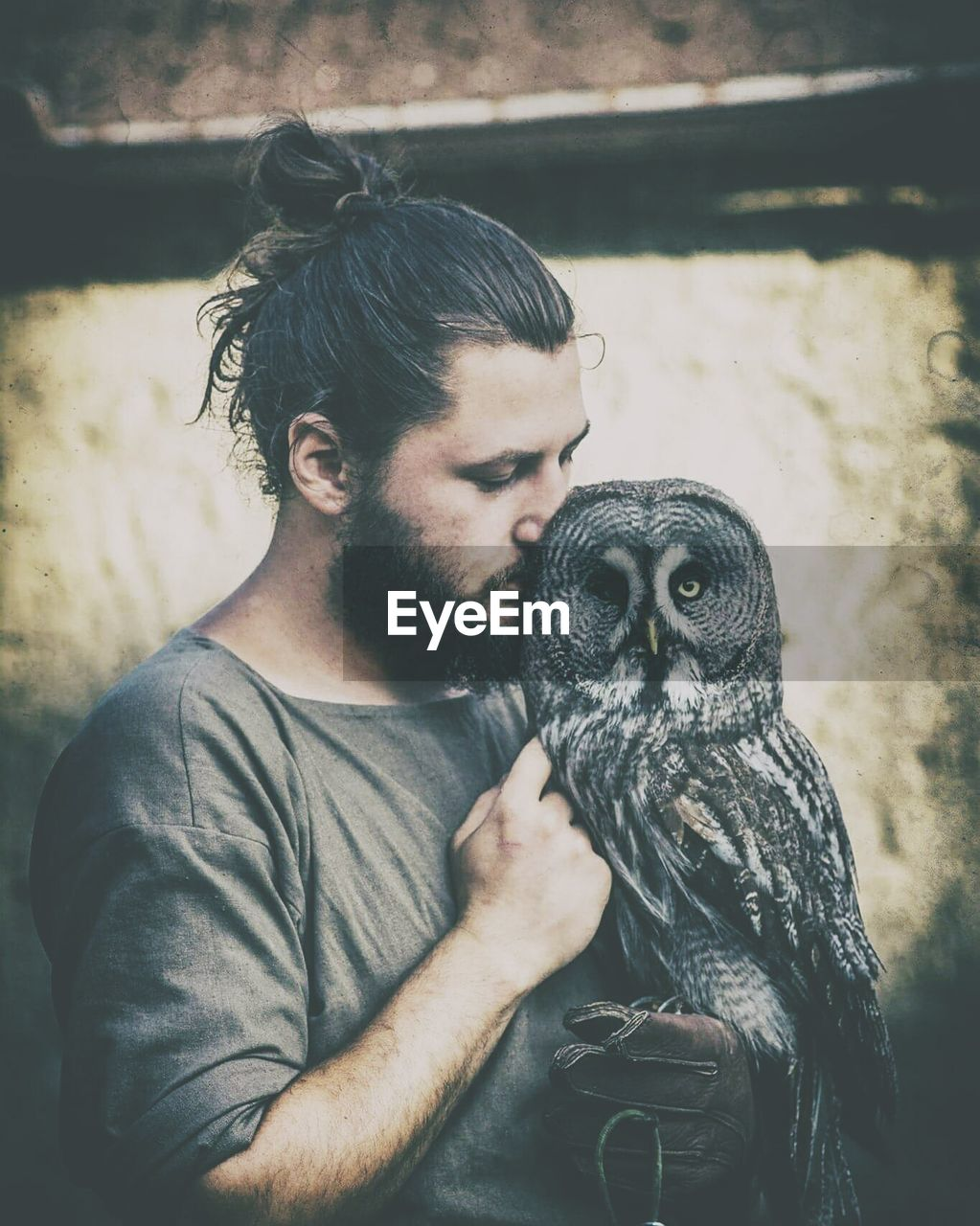 one animal, animal themes, mammal, pets, monkey, casual clothing, real people, young adult, holding, one person, young men, animal wildlife, lifestyles, sitting, dog, day, domestic animals, outdoors, bird, people