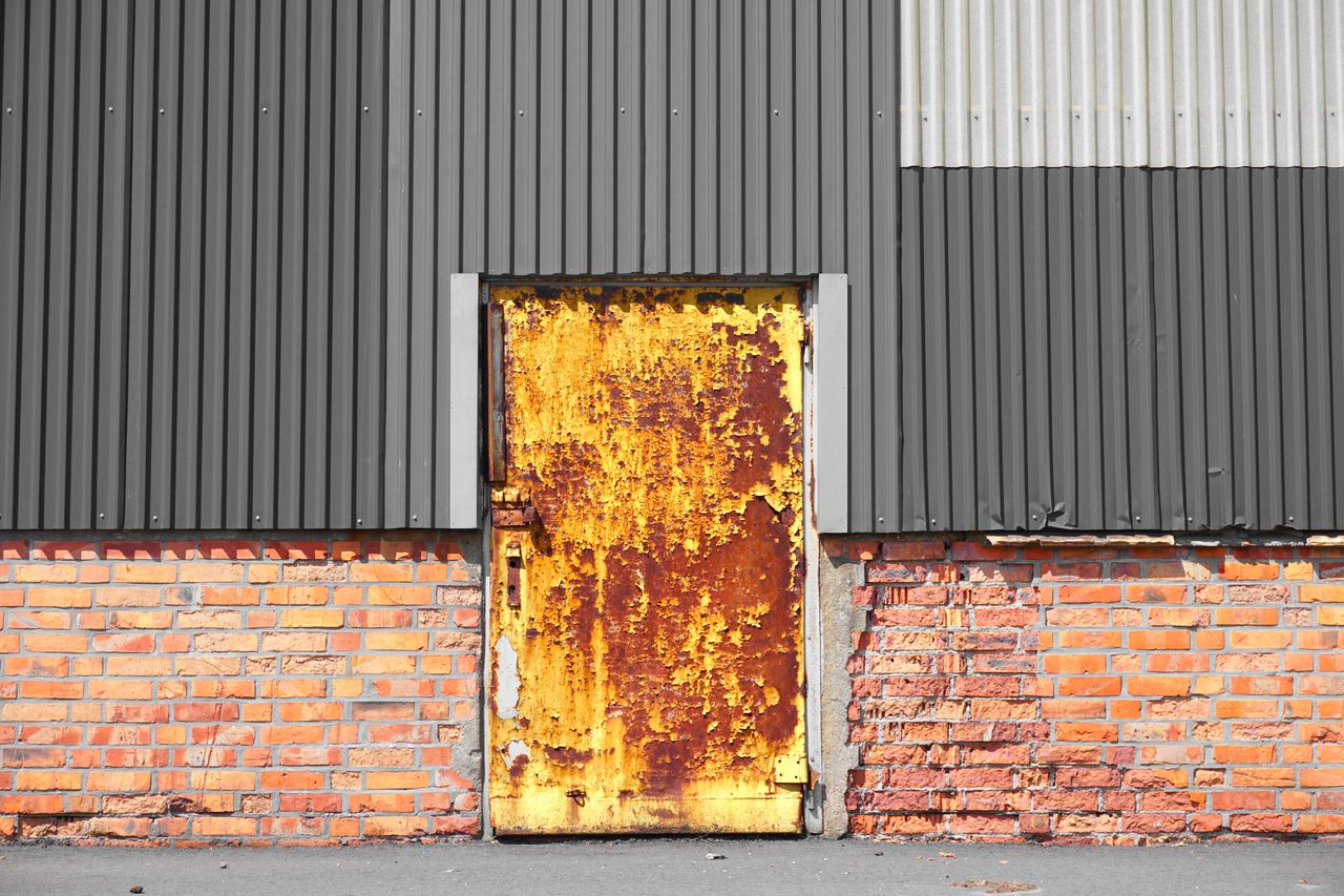 architecture, wall - building feature, metal, brick wall, building exterior, built structure, brick, closed, no people, day, yellow, iron, wall, pattern, corrugated iron, door, entrance, outdoors, city, backgrounds, corrugated, garage, sheet metal