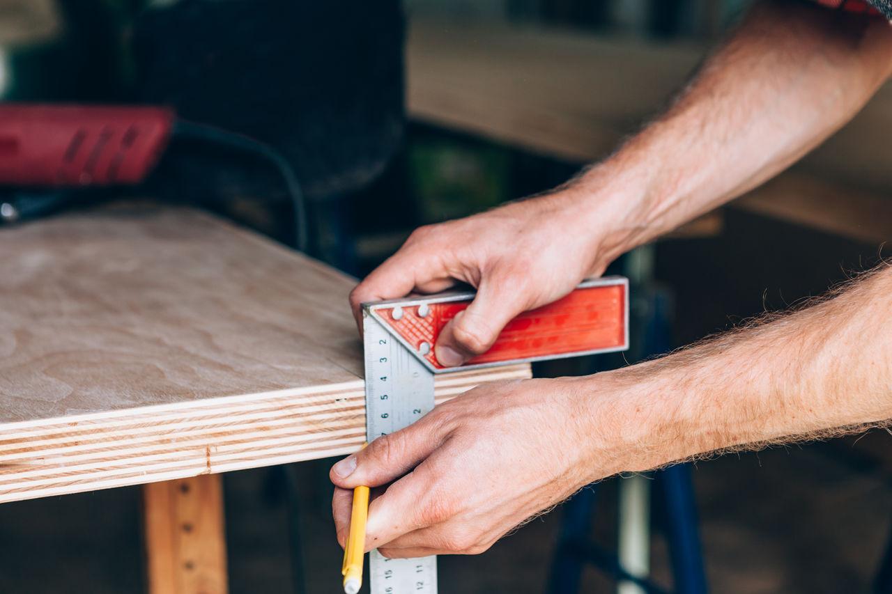 Cropped Hands Of Carpenter Measuring Wood At Workshop